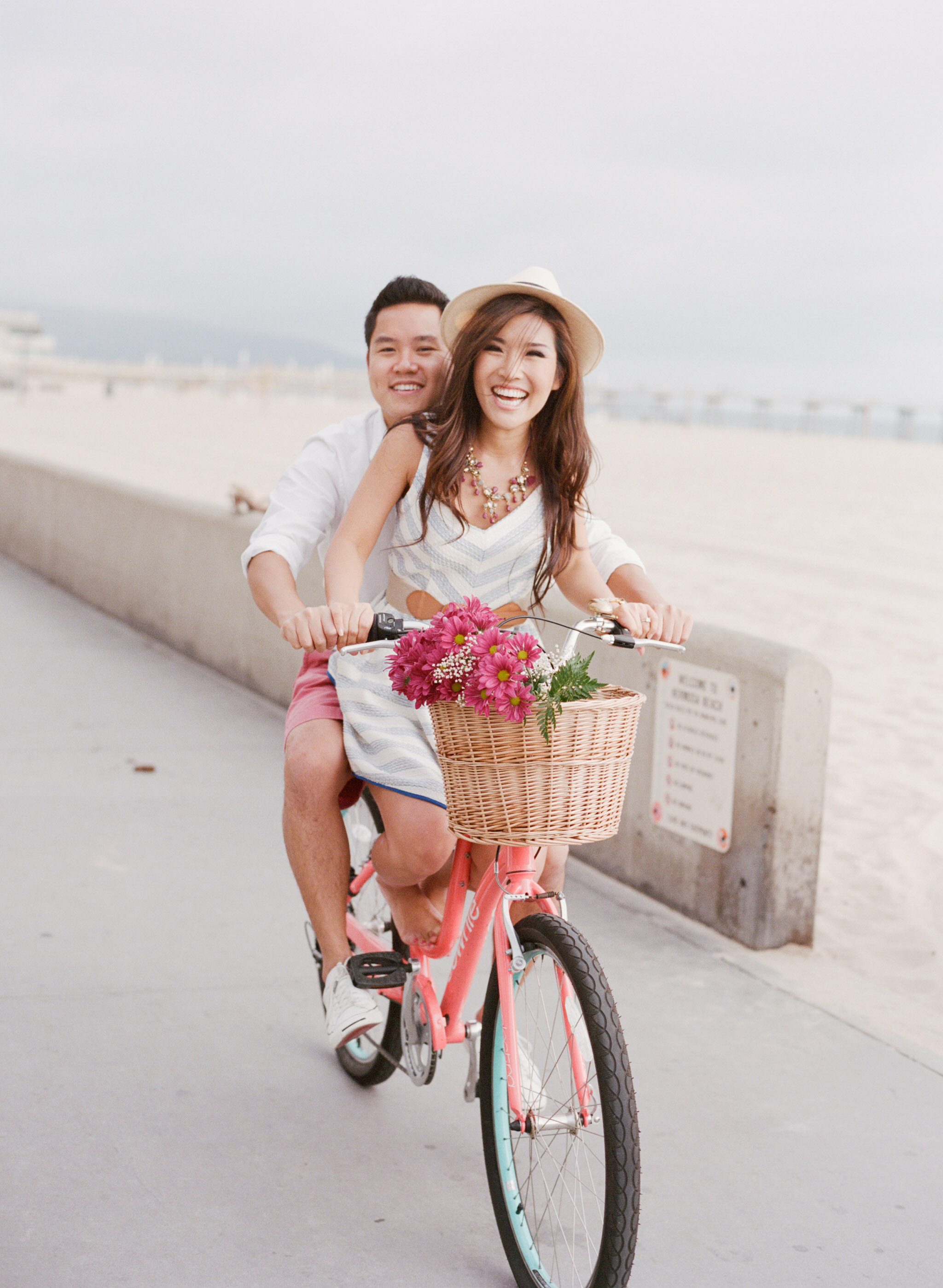 Couple rides pink bicycle together with basket of flowers down Hermosa Beach boardwalk at an engagement session with Sylvie Gil.