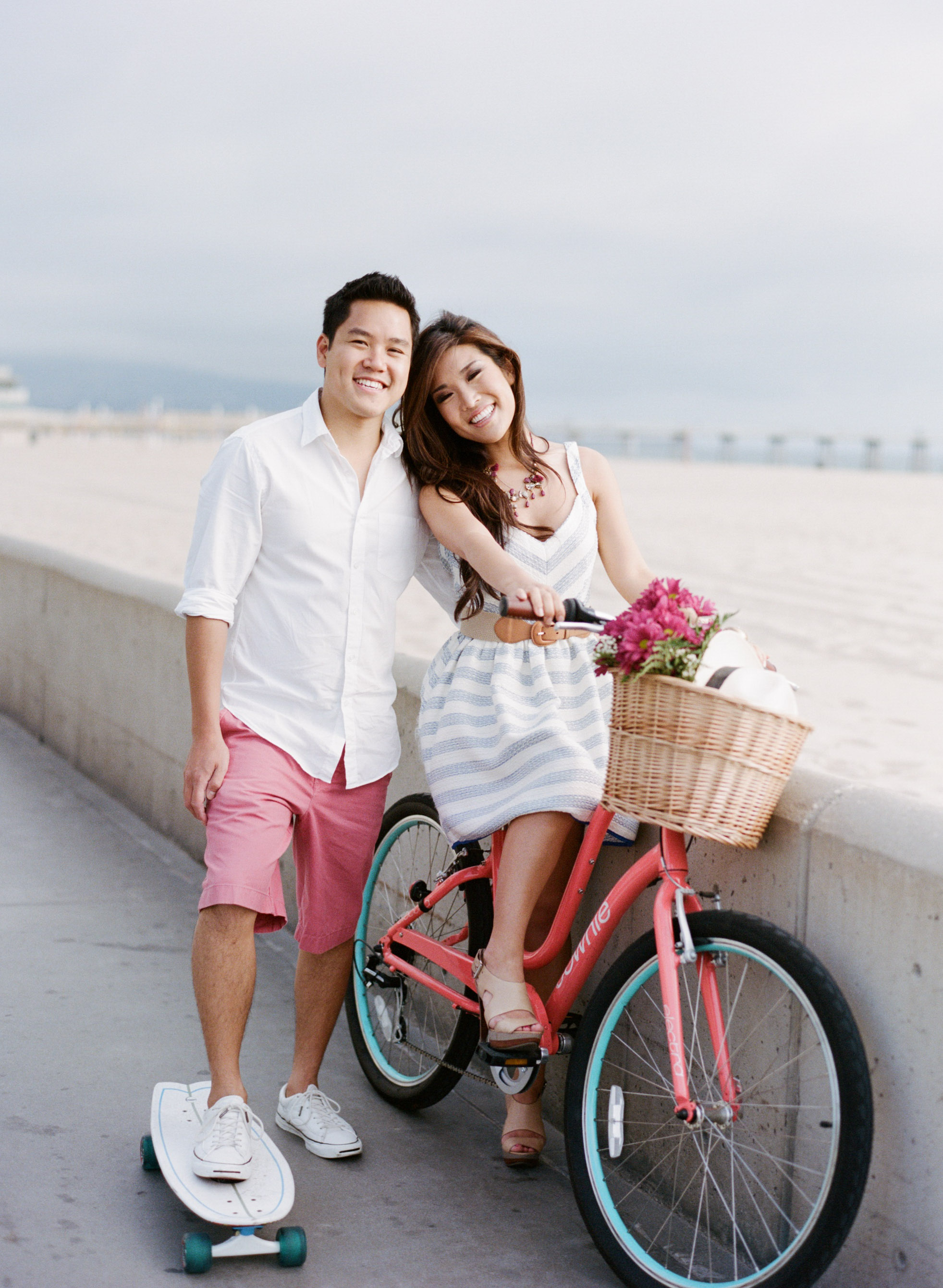 Couple with bicycle and skateboard on Hermosa Beach boardwalk during an engagment shoot with Sylvie Gil.