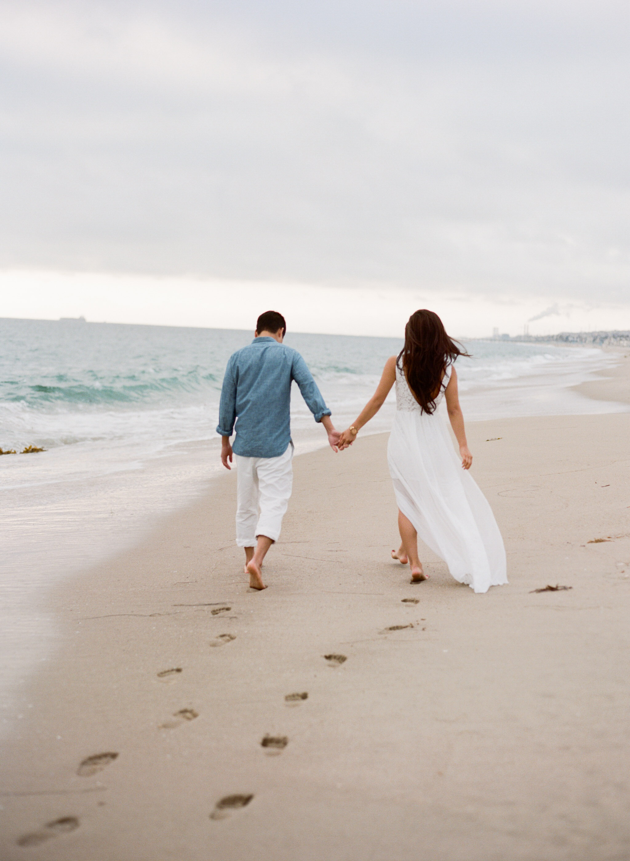 A couple leaves their footprints in the wet sand during an engagement shoot with Sylvie Gil at Hermosa Beach.