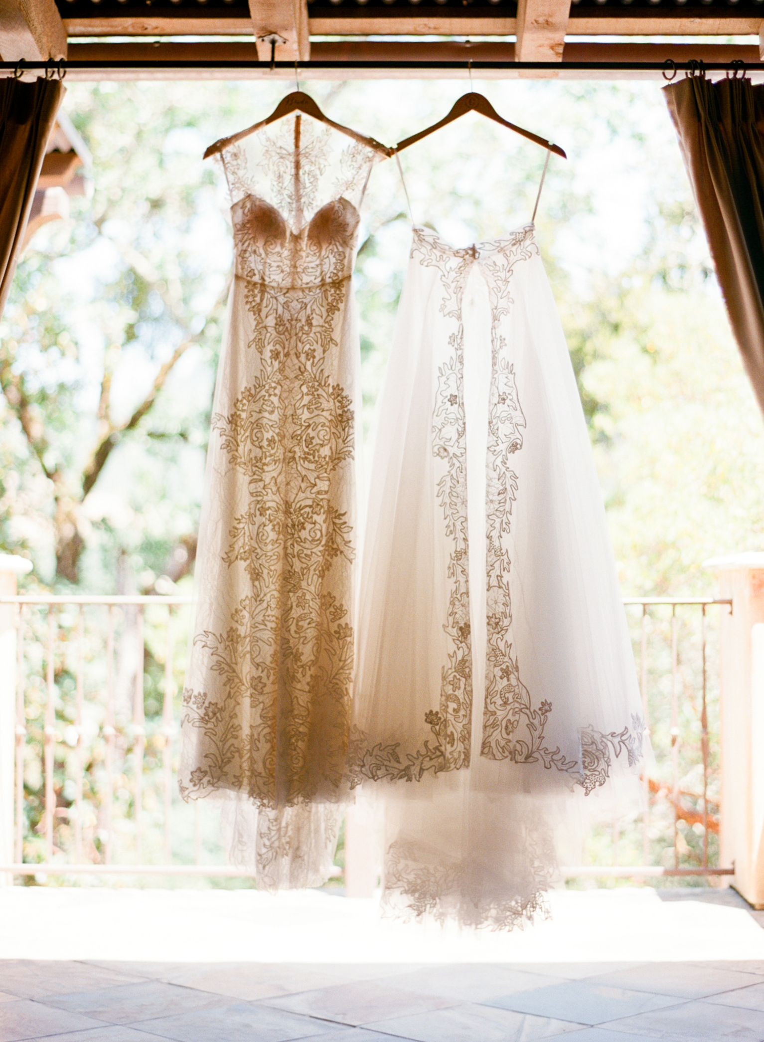 Caroline's stunning two piece Monique Lhuillier lace gown hangs on rafters before the ceremony; photo by Sylvie