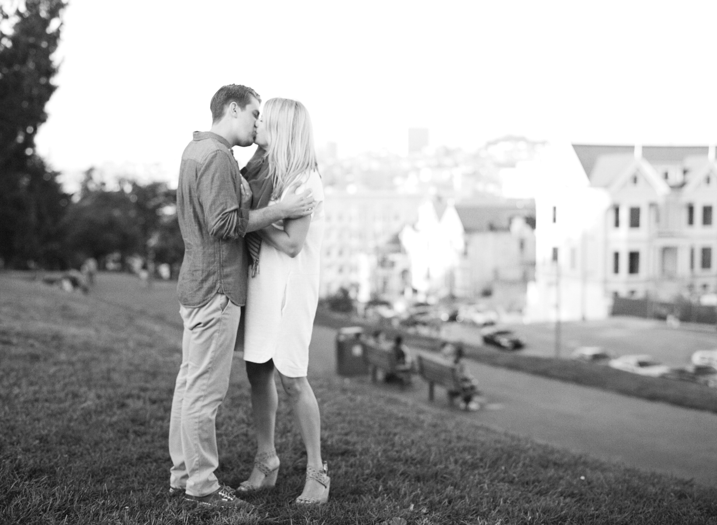 A couple kisses at Alamo Square Park in San Francisco during an engagement session with Sylvie Gil.