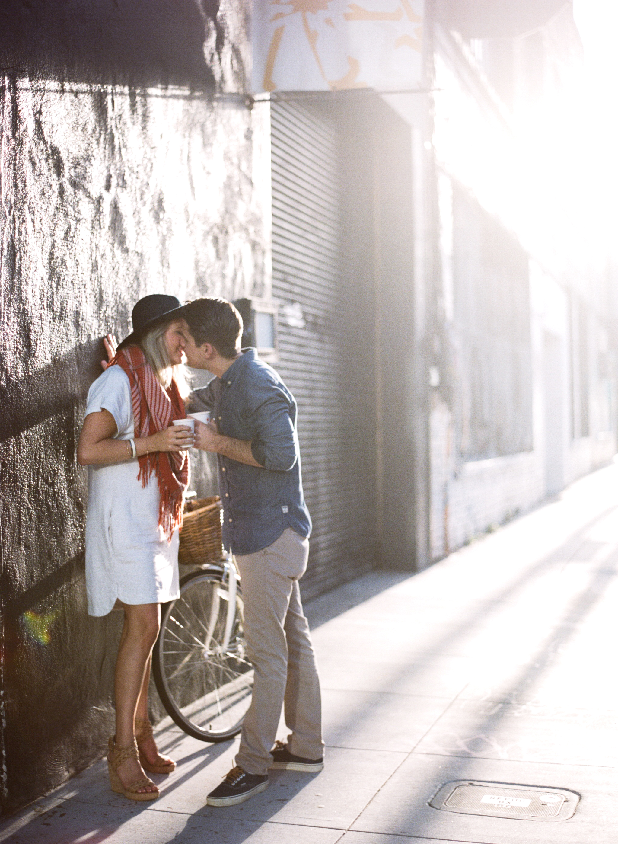 A couple shares a kiss over coffee in a San Francisco alley during an engagement shoot with Sylvie Gil.