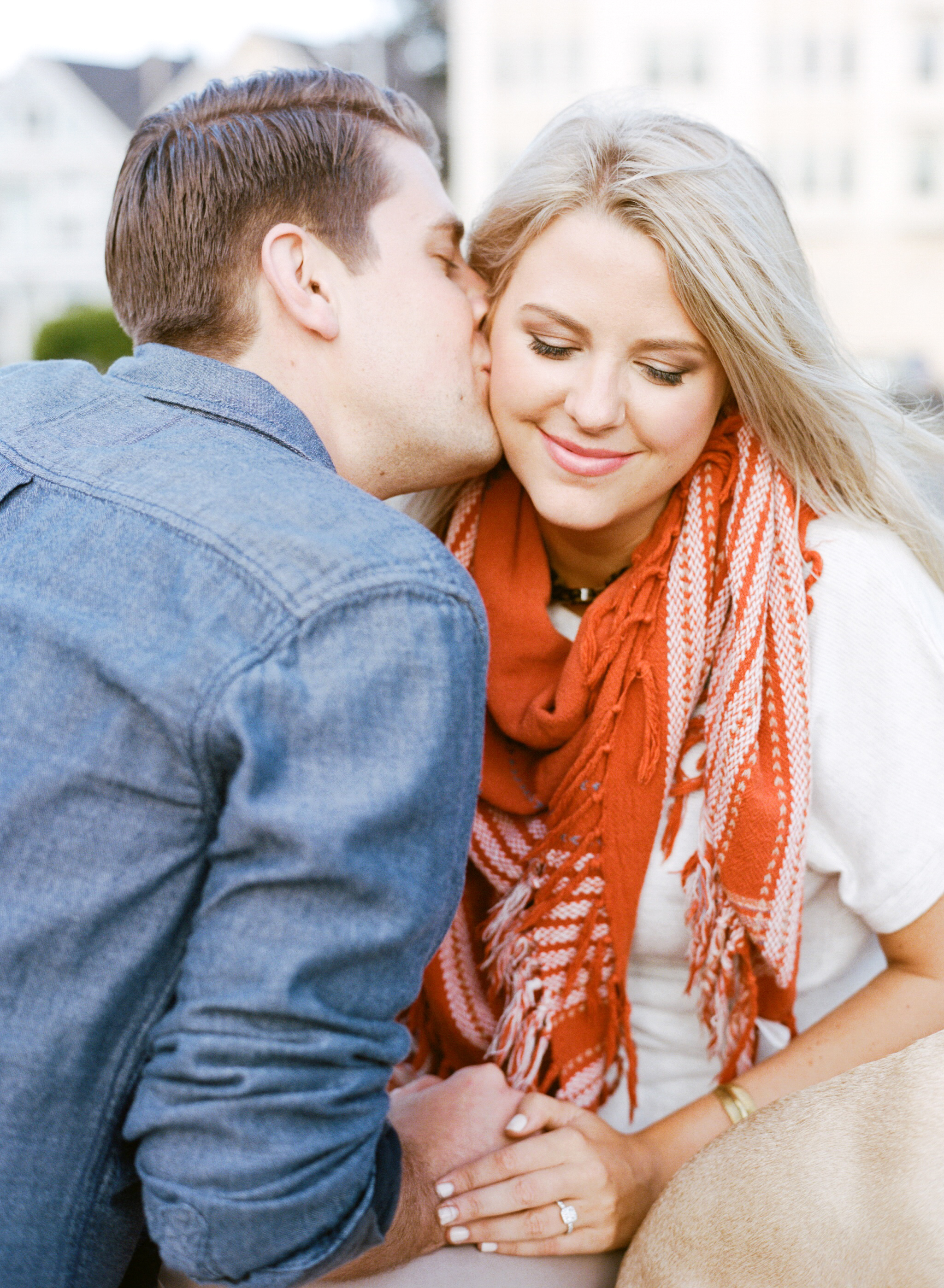 A groom-to-be kisses his fiancee on the grass at Alamo Square Park during an engagement shoot with Sylvie Gil.