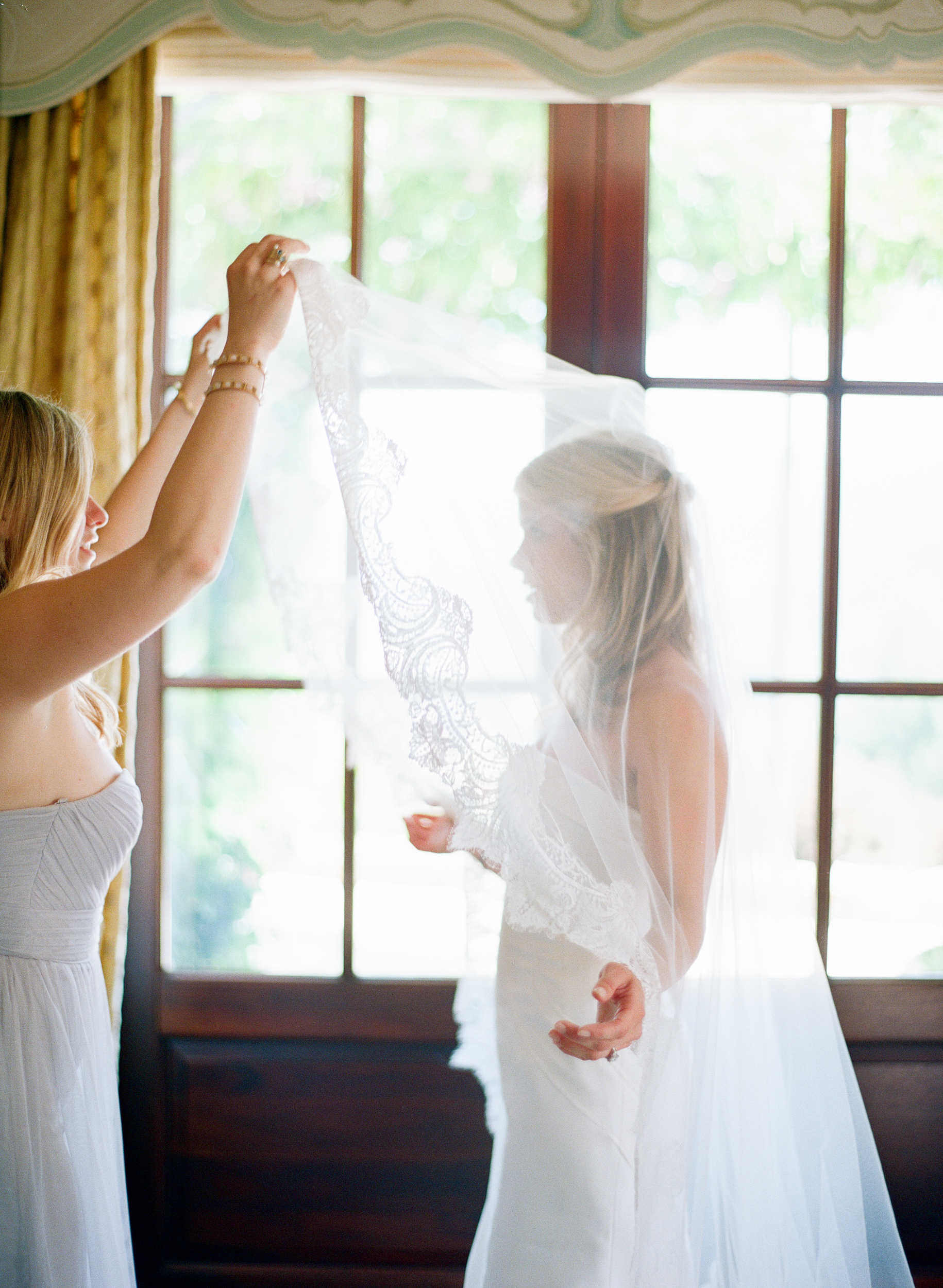 Sarah's bridesmaids lift her beautiful lace veil over her head; photo by Sylvie Gil.