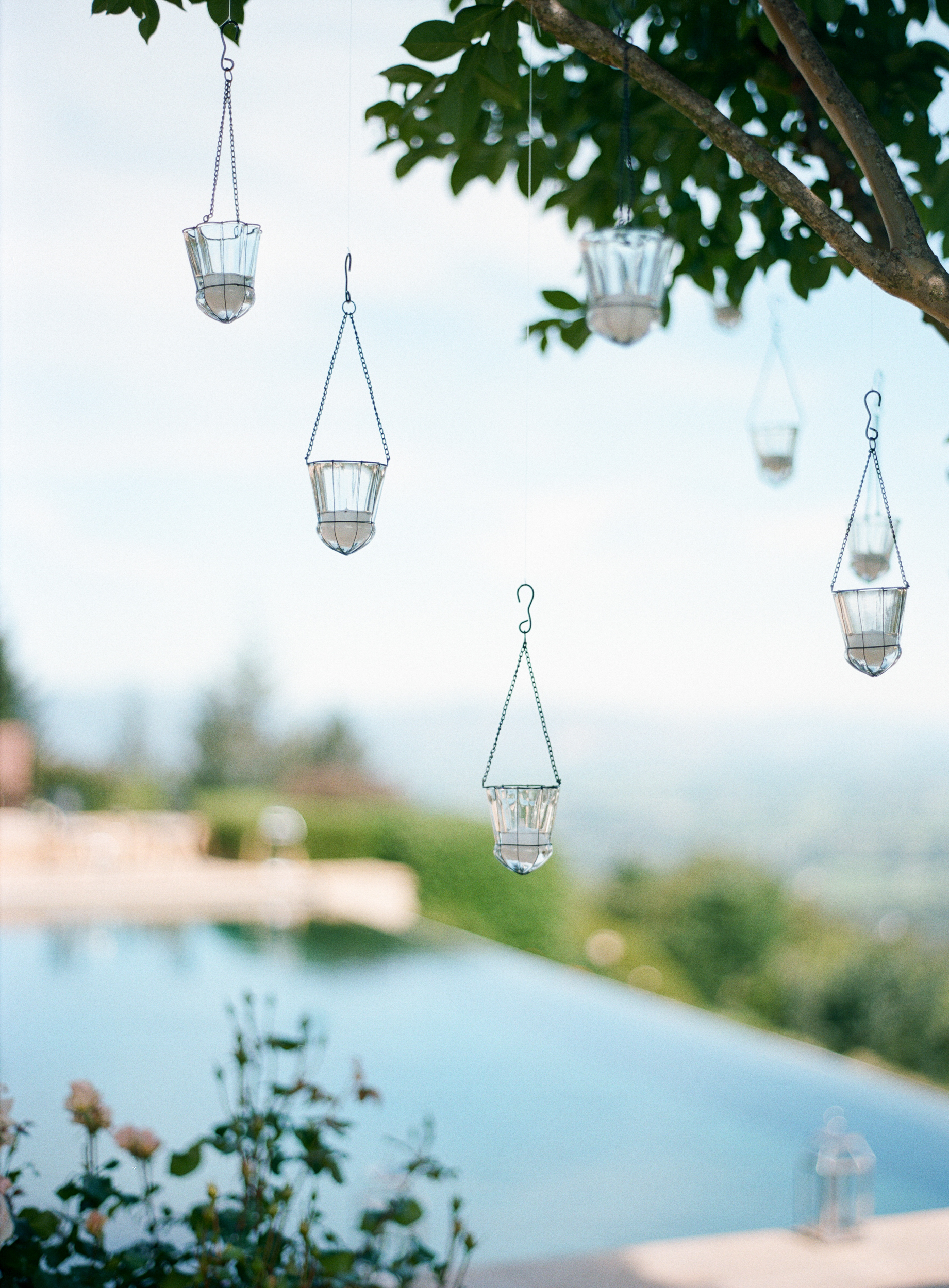 Votives hanging from trees at the outdoor reception by the pool; photo by Sylvie Gil