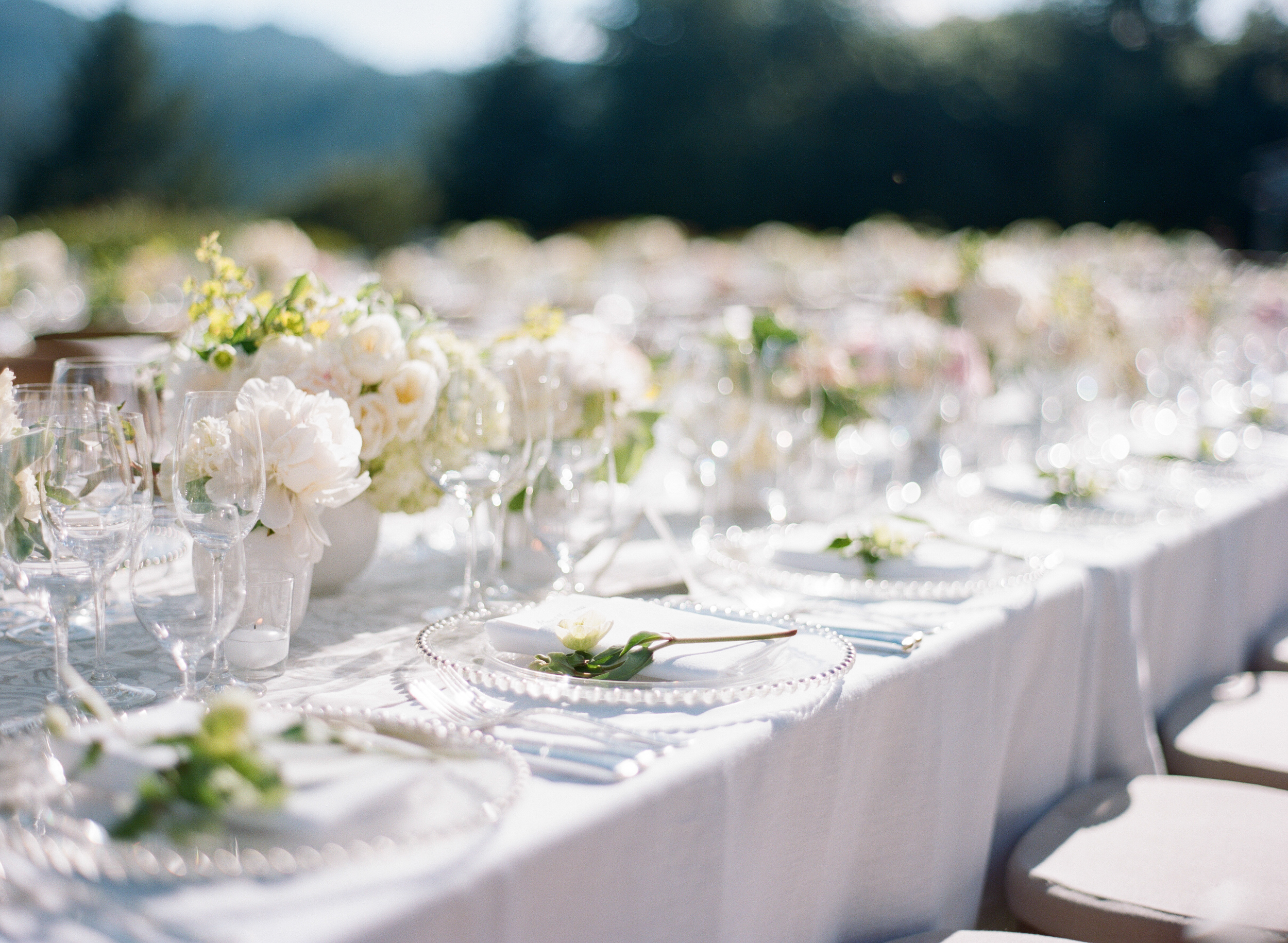White and light pastel centerpieces adorn the reception tables; photo by Sylvie Gil