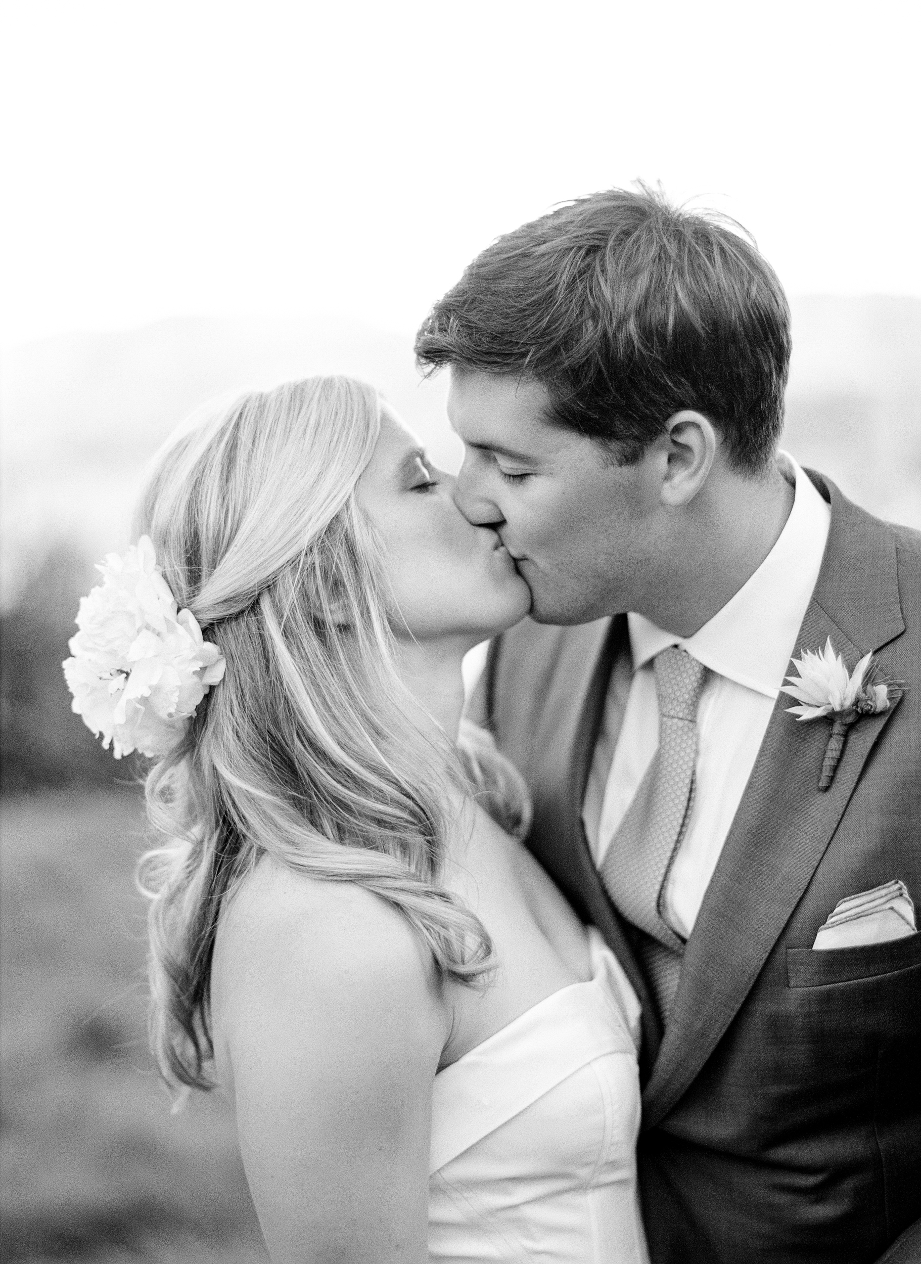 Newly married Sarah and James share a kiss after the ceremony for a couple portrait session; photo by Sylvie Gil
