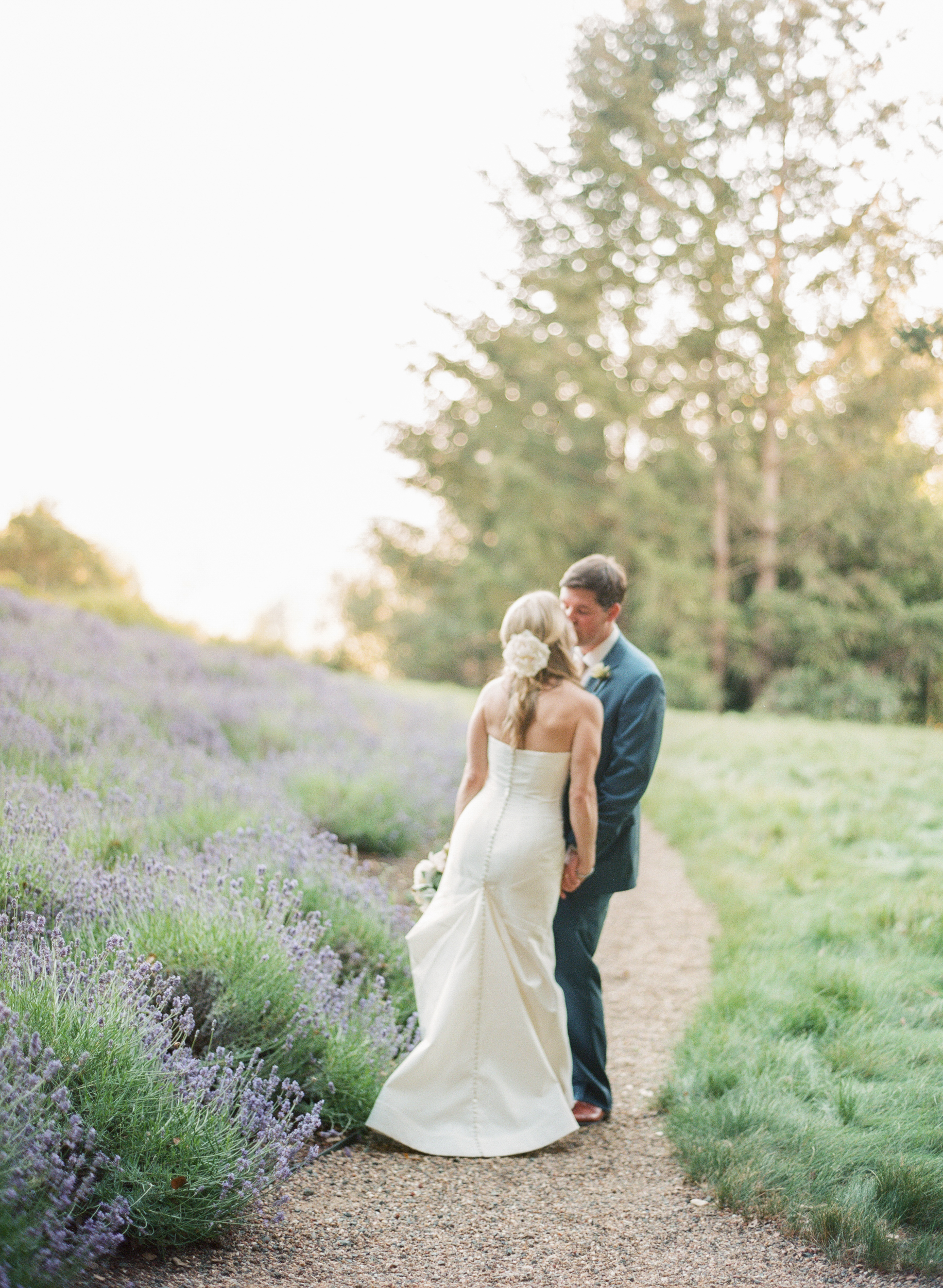 The newly married couple shares a quiet moment next to a field of lavender; photo by Sylvie Gil