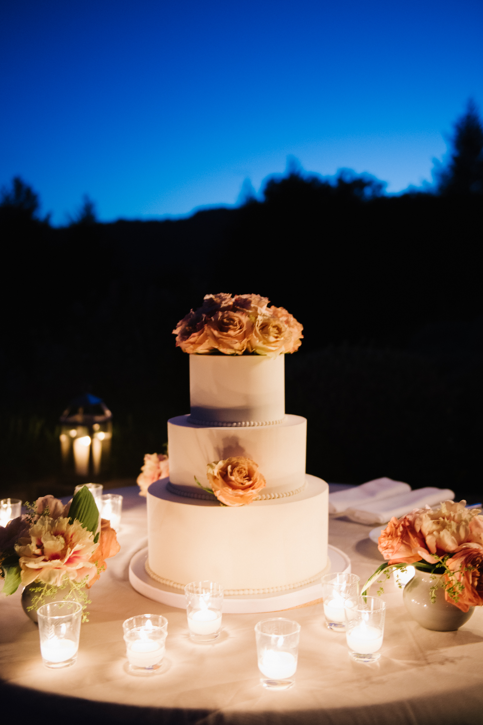The wedding cake matched the elegance and romance of the evening, surrounded by tea lights and blushing roses; photo by Sylvie Gil