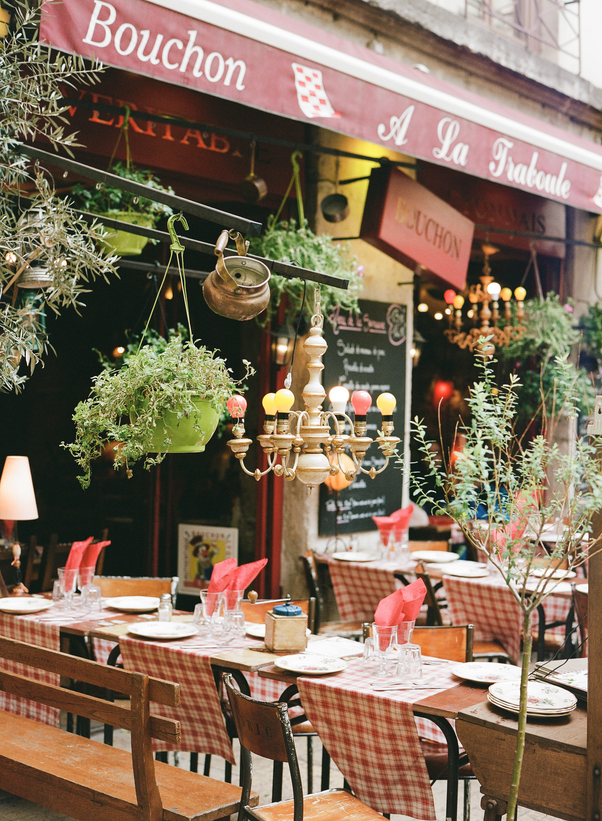 A cute outdoor cafe in Lyon displaying checkered tablecloths and a friendly atmosphere; photo by Sylvie Gil