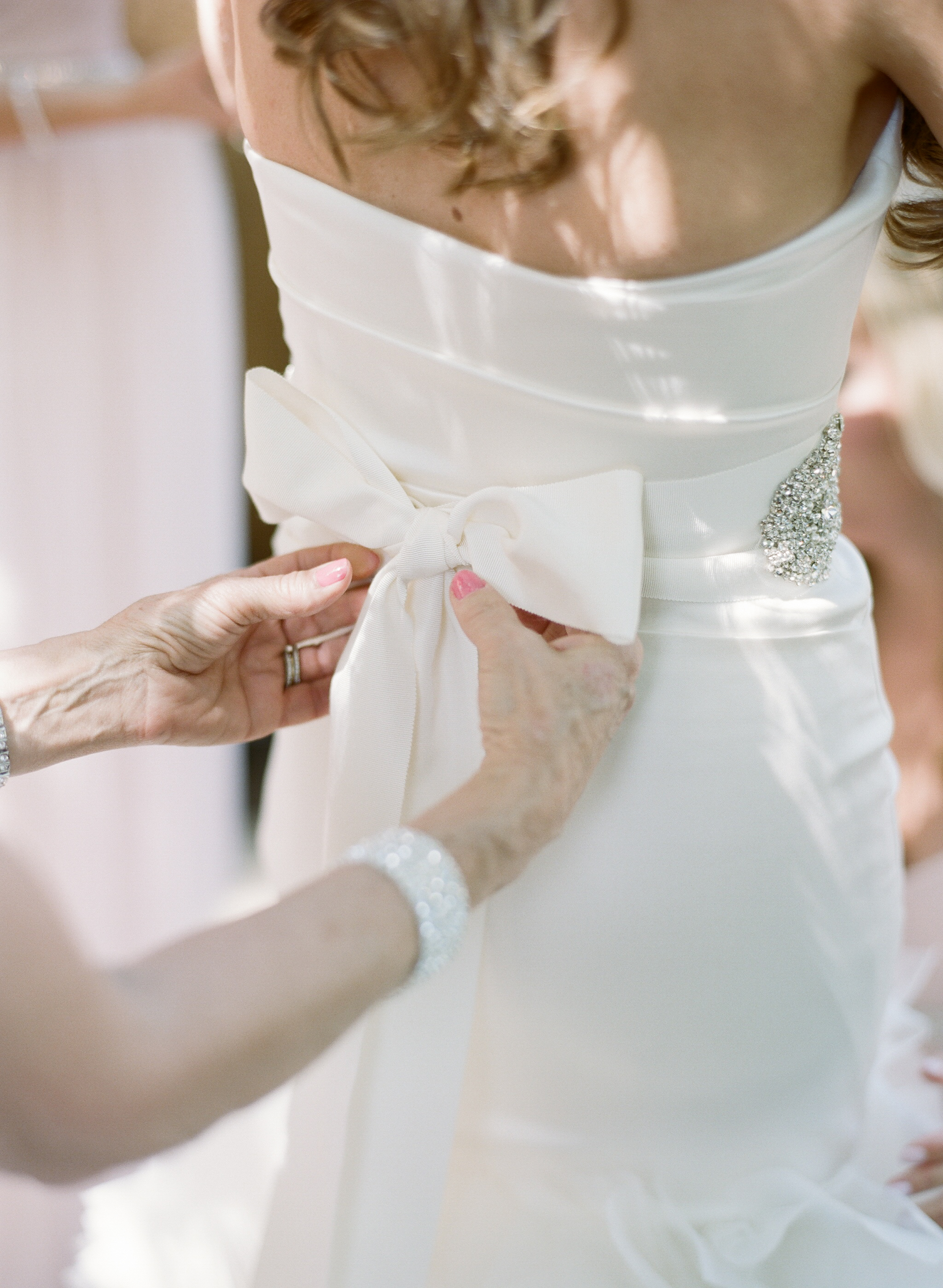 A member of the bridal party ties the gown on the back of Lauren's elegant strapless wedding gown; photo by Sylvie Gil