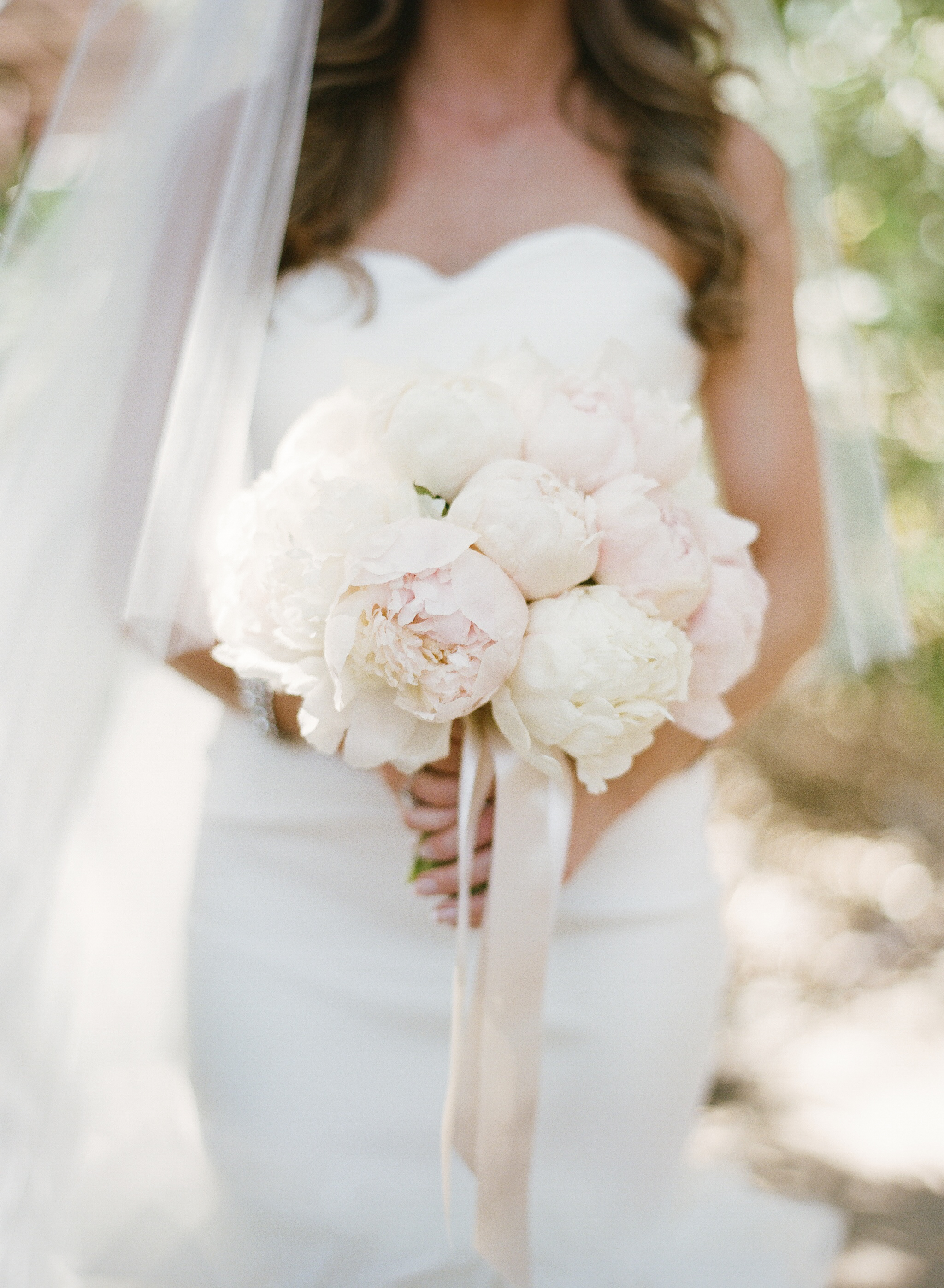 A glowing bride holds her bouquet of white and blush florals, wearing a strapless sweetheart-neckline gown; photo by Sylvie Gil