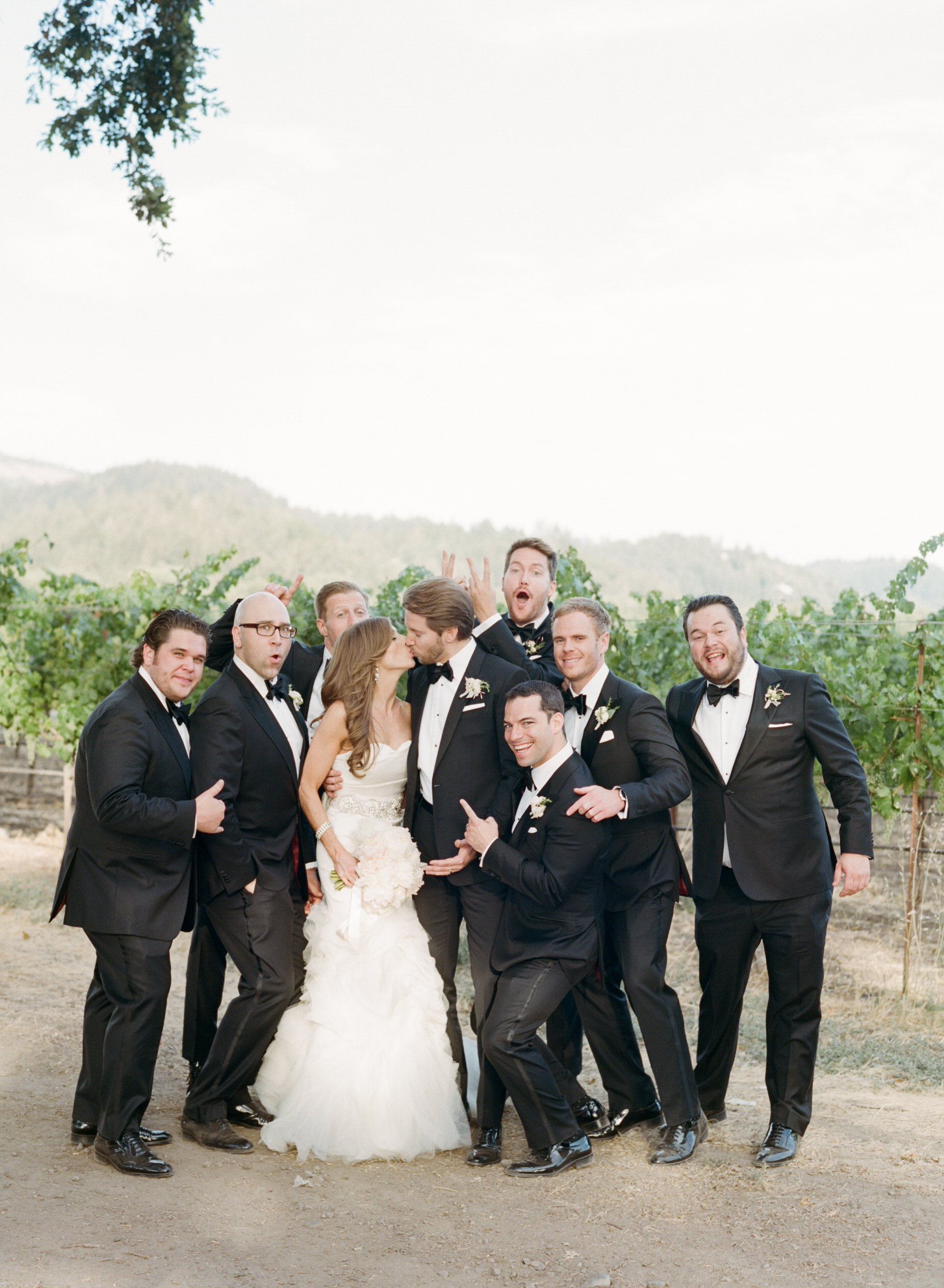 Michael kisses his bride, surrounded by his goofy groomsmen, posing for a silly shot; photo by Sylvie Gil
