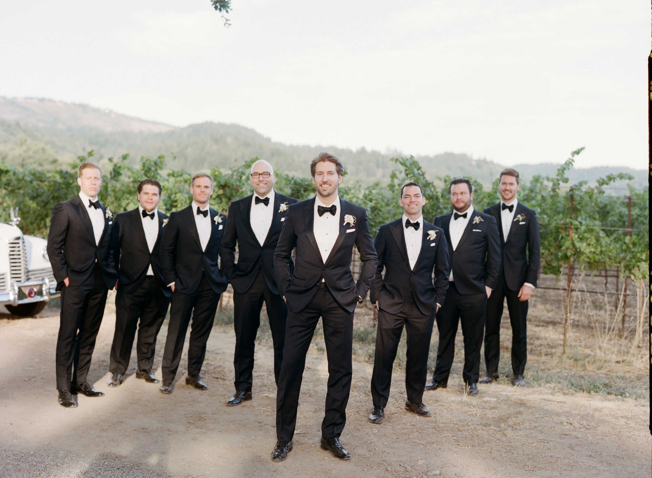 Michael poses with his groomsmen, all handsome in black tuxedos; photo by Sylvie Gil