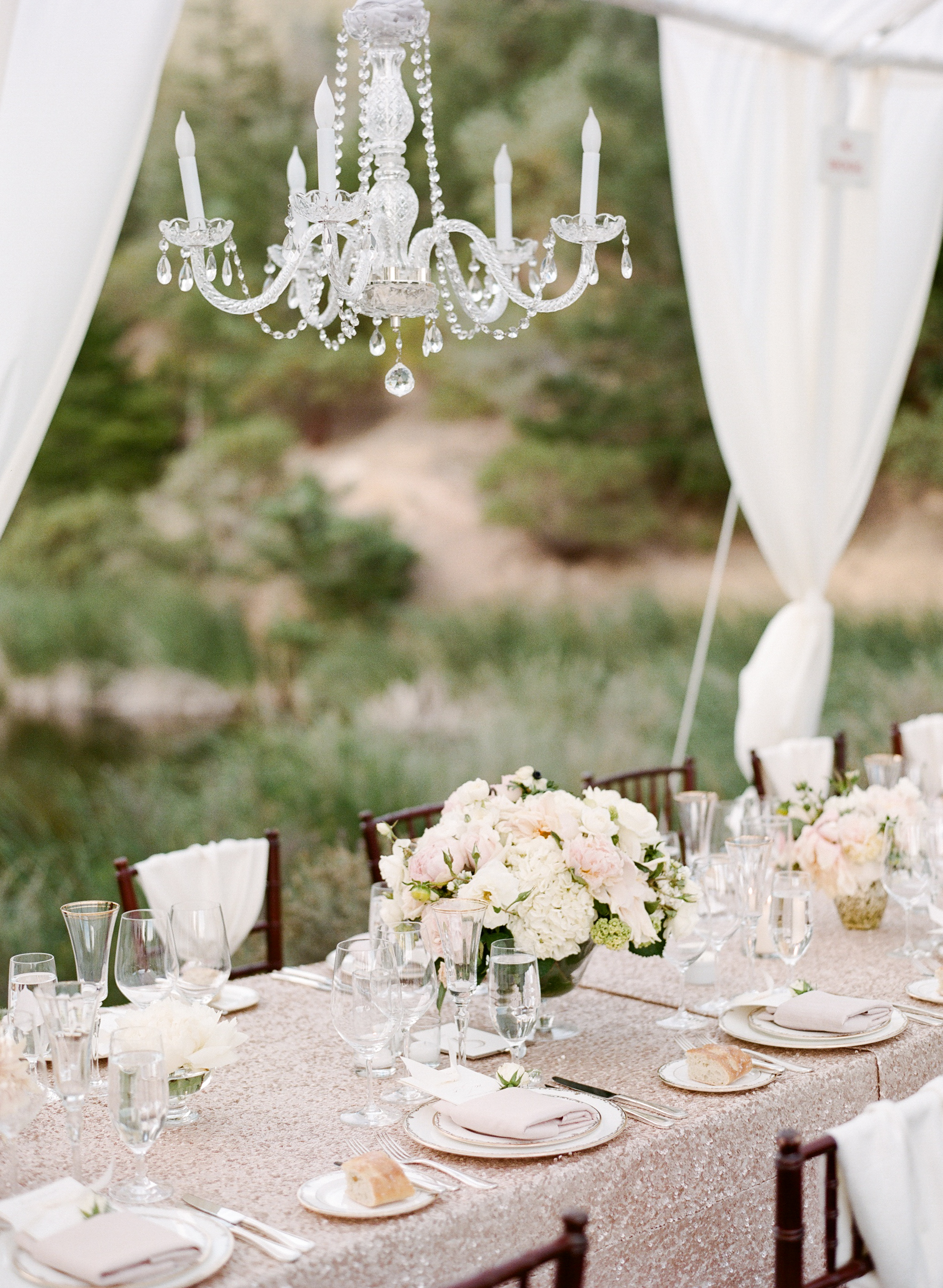 The canopied outdoor reception boasted glittering tablecloths and elegant chandeliers, as well as matching blush centerpieces; photo by Sylvie Gil