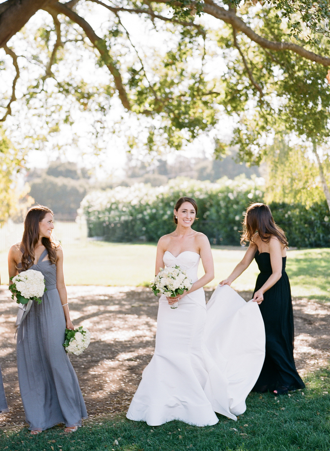 Bridesmaids in a range of navy, black, and gray gowns help with the train of the bride's Oscar de la Renta wedding gown; photo by Sylvie Gil