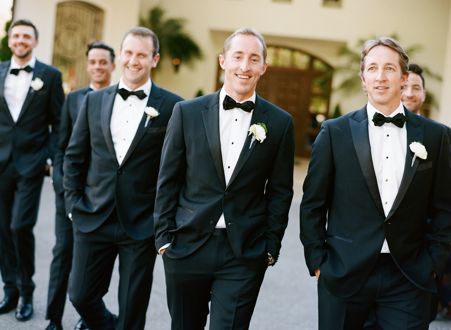 The groom walks toward the camera surrounded by his dapper groomsmen, dressed in black tuxedos; photo by Sylvie Gil