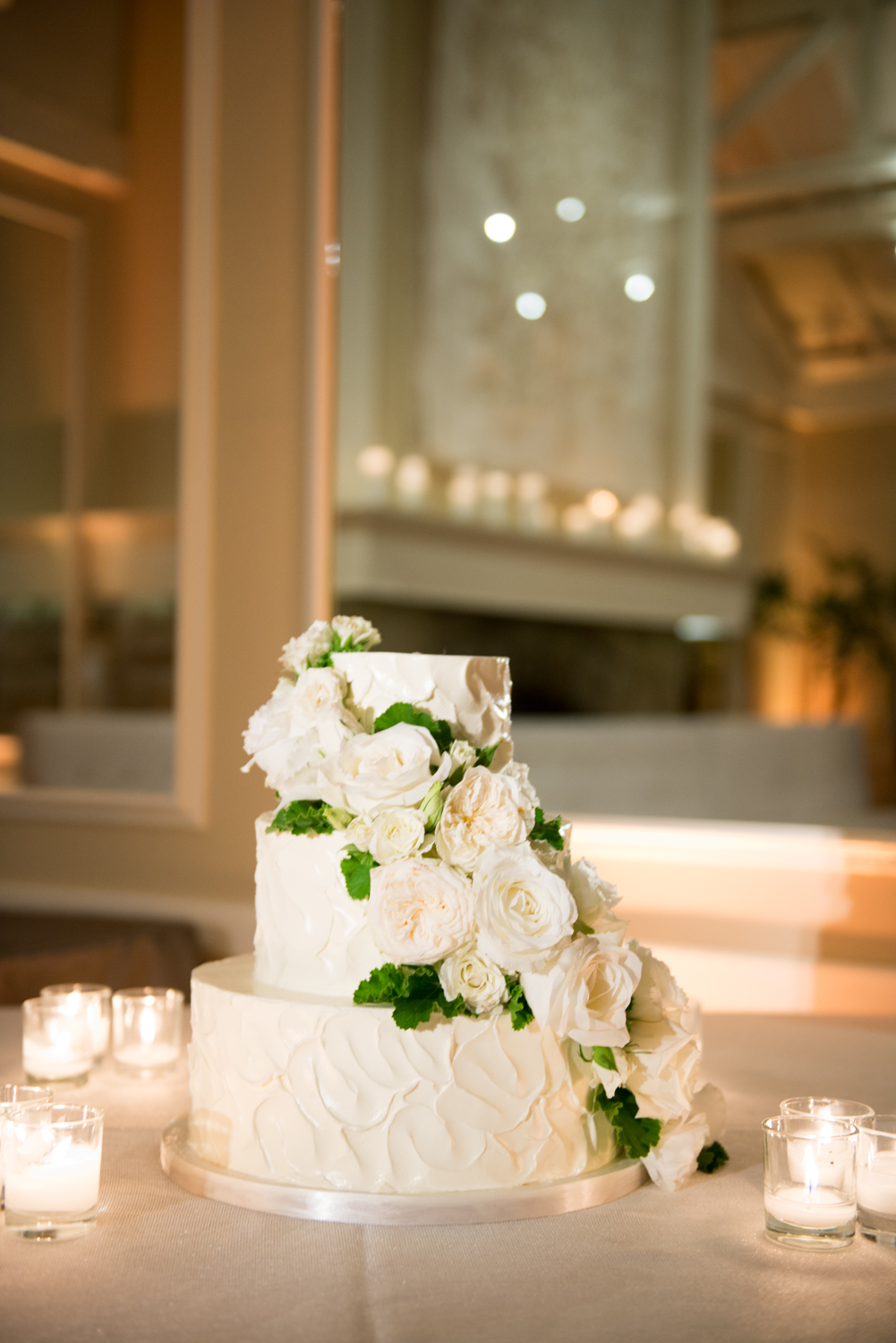 A three layer wedding cake surrounded by votive candles and draped with elegant white florals; photo by Sylvie Gil