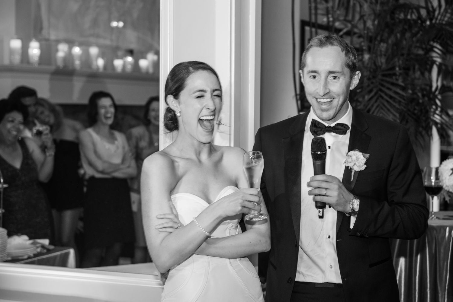 Palpable joy during the groom's champagne toast seen in the bride's laughter; photo by Sylvie Gil