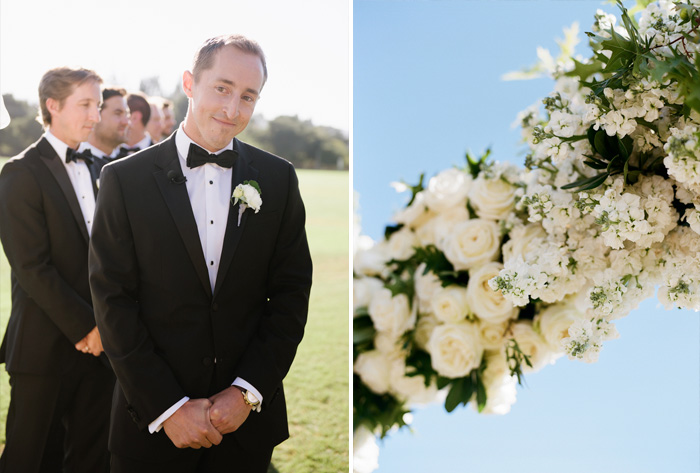The groom waits for his bride under a white floral arbor during the outdoor ceremony; photo by Sylvie Gil