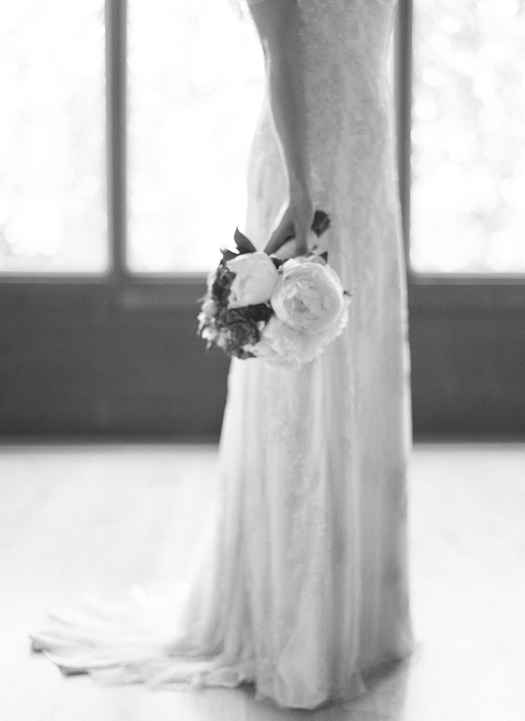 A blurry, romantic shot of the bride holding her bouquet before the wedding; photo by Sylvie Gil