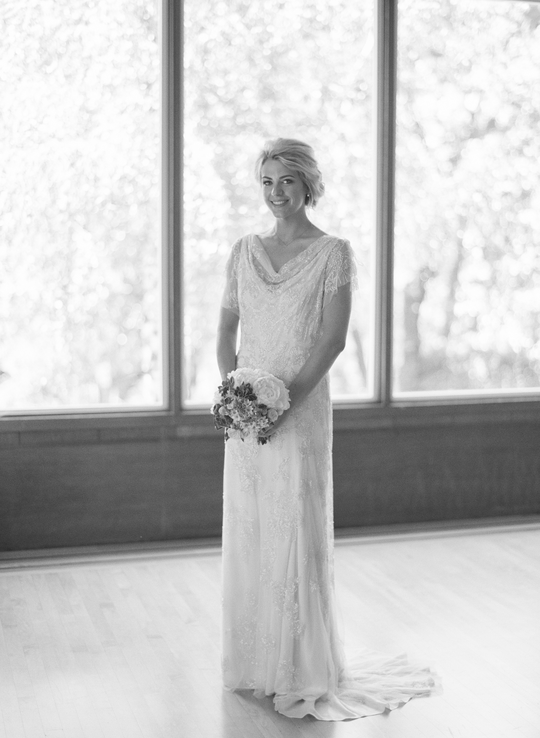 The bride stands in an elegantly draped, lace sheath dress before the wedding, photo by Sylvie Gil