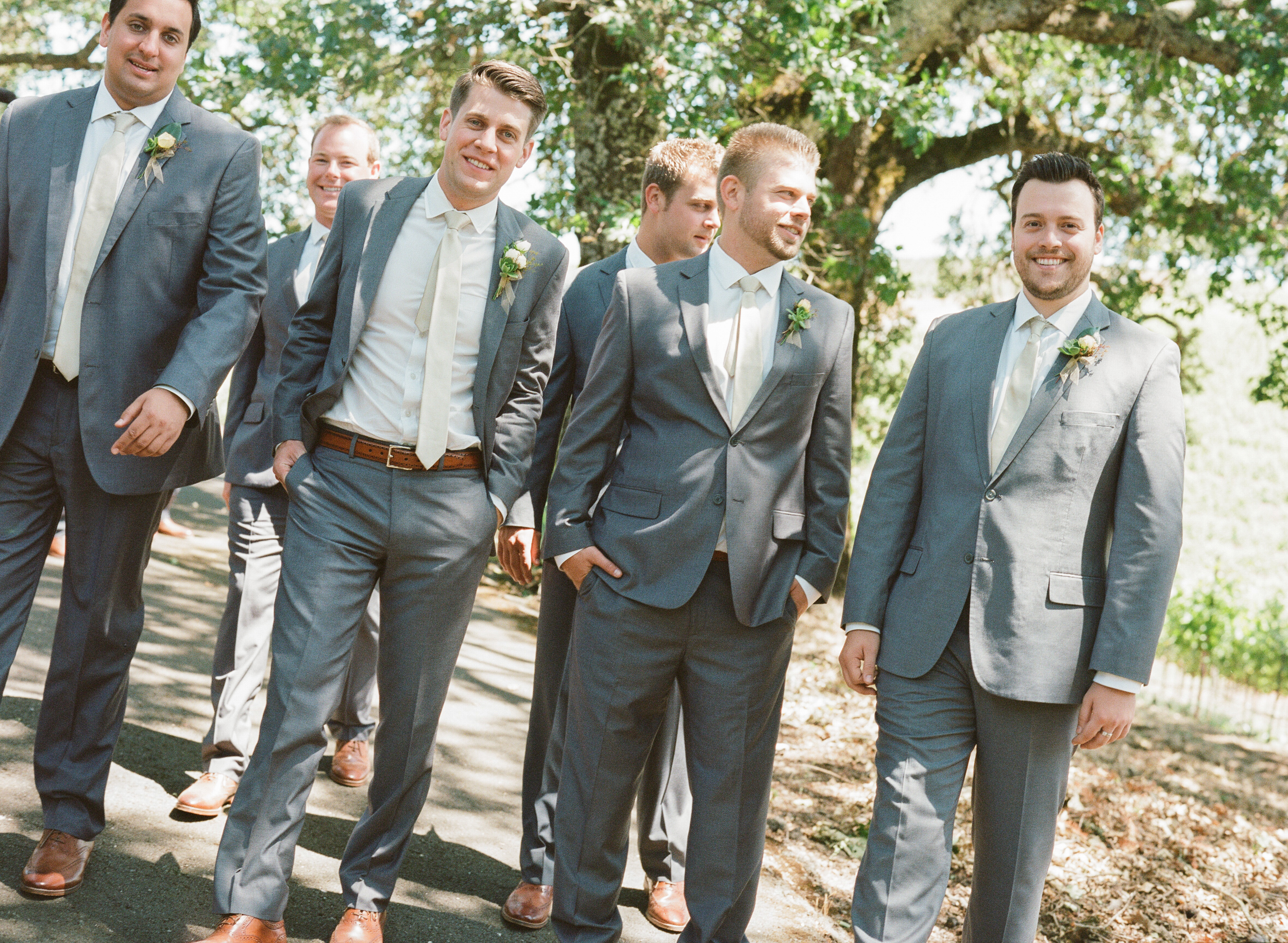 The dapper groomsmen walk toward the camera together in grey suits and white ties; photo by Sylvie Gil