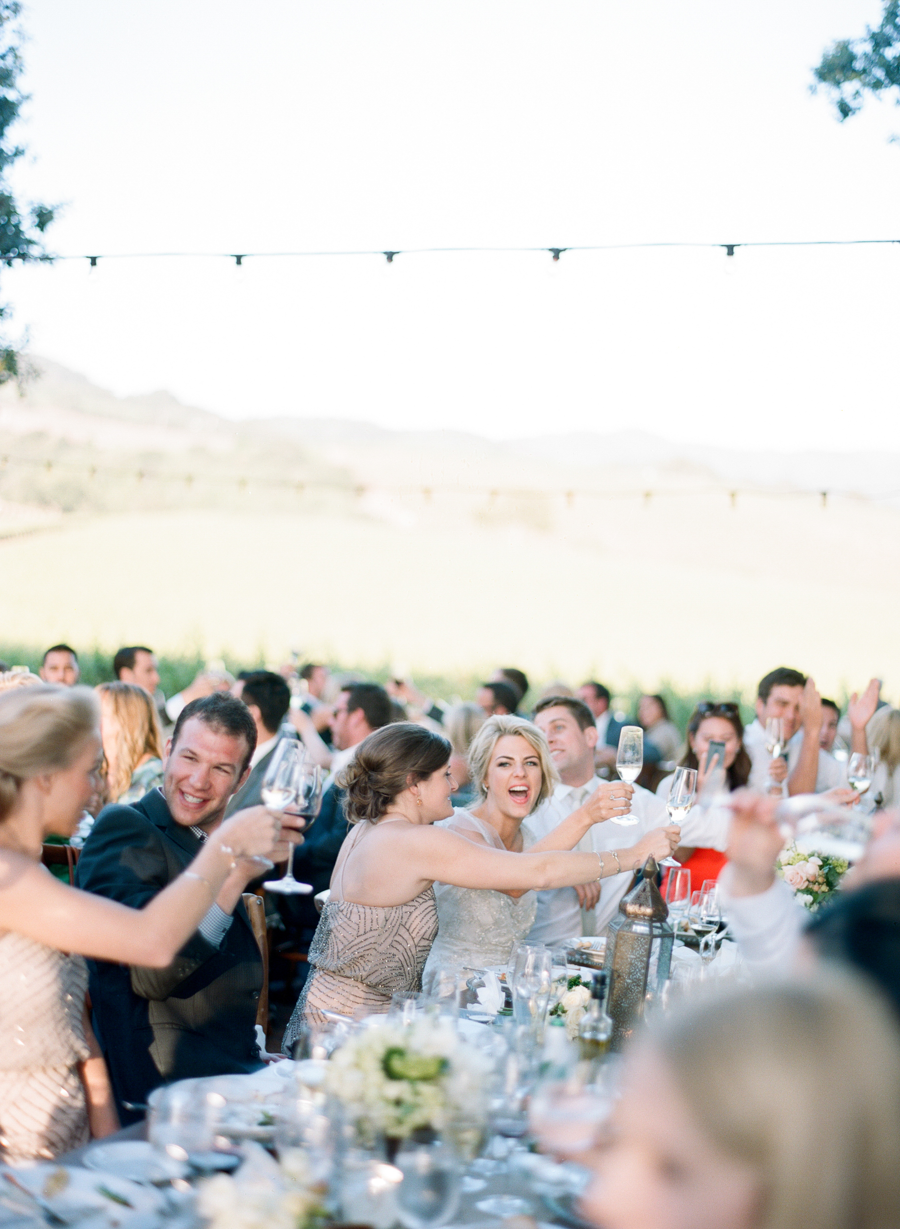 The wedding reception is a joyous affair filled with laughter and clinking champagne flutes; photo by Sylvie Gil