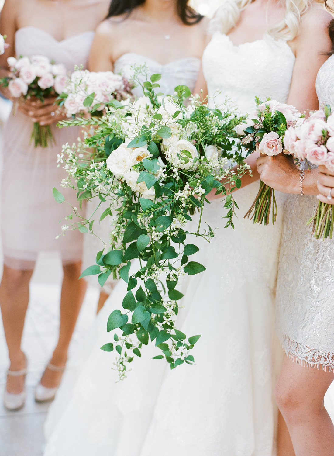 Megan holds her lush, cascading bouquet, surrounded by pink-themed bridesmaids with rosy bouquets; photo by Sylvie Gil