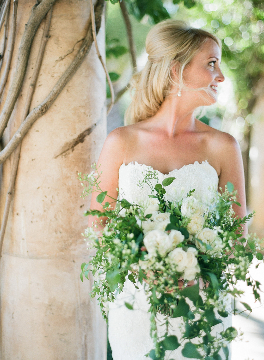 A romantic shot of the bride looking at her groom over her shoulder, dressed in a sweetheart neckline lace dress, holding a cascading bouquet; photo by Sylvie Gil