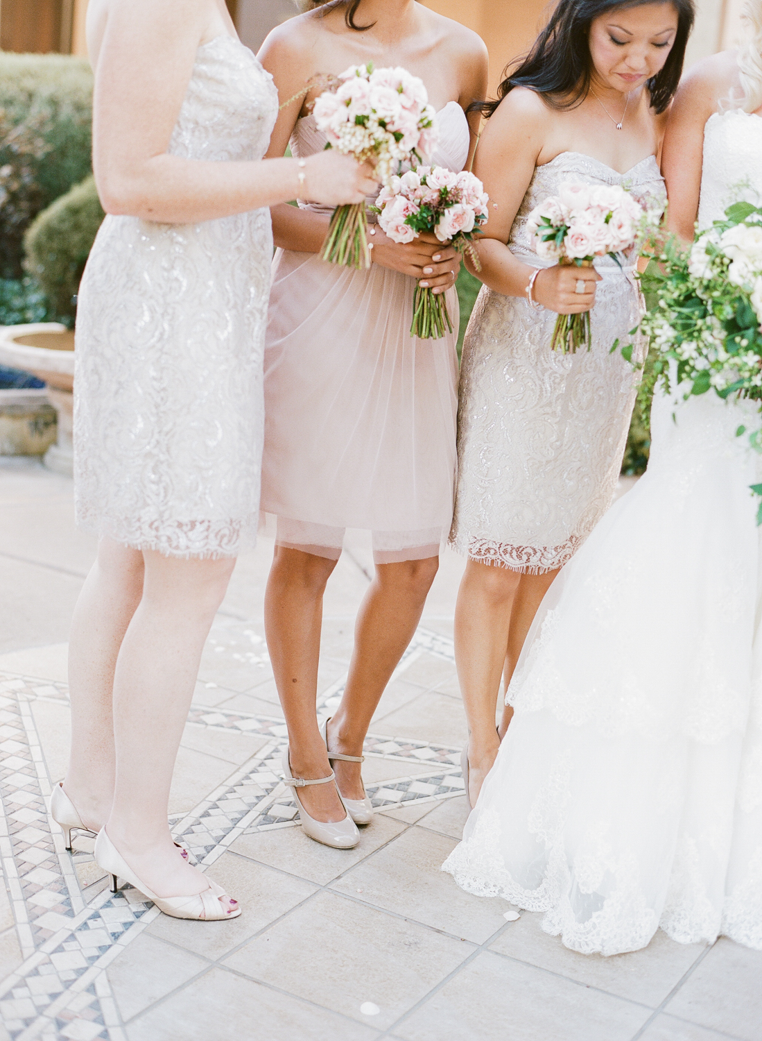 Bridesmaids in varied by related dresses of chiffon and lace cream and blush; photo by Sylvie Gil