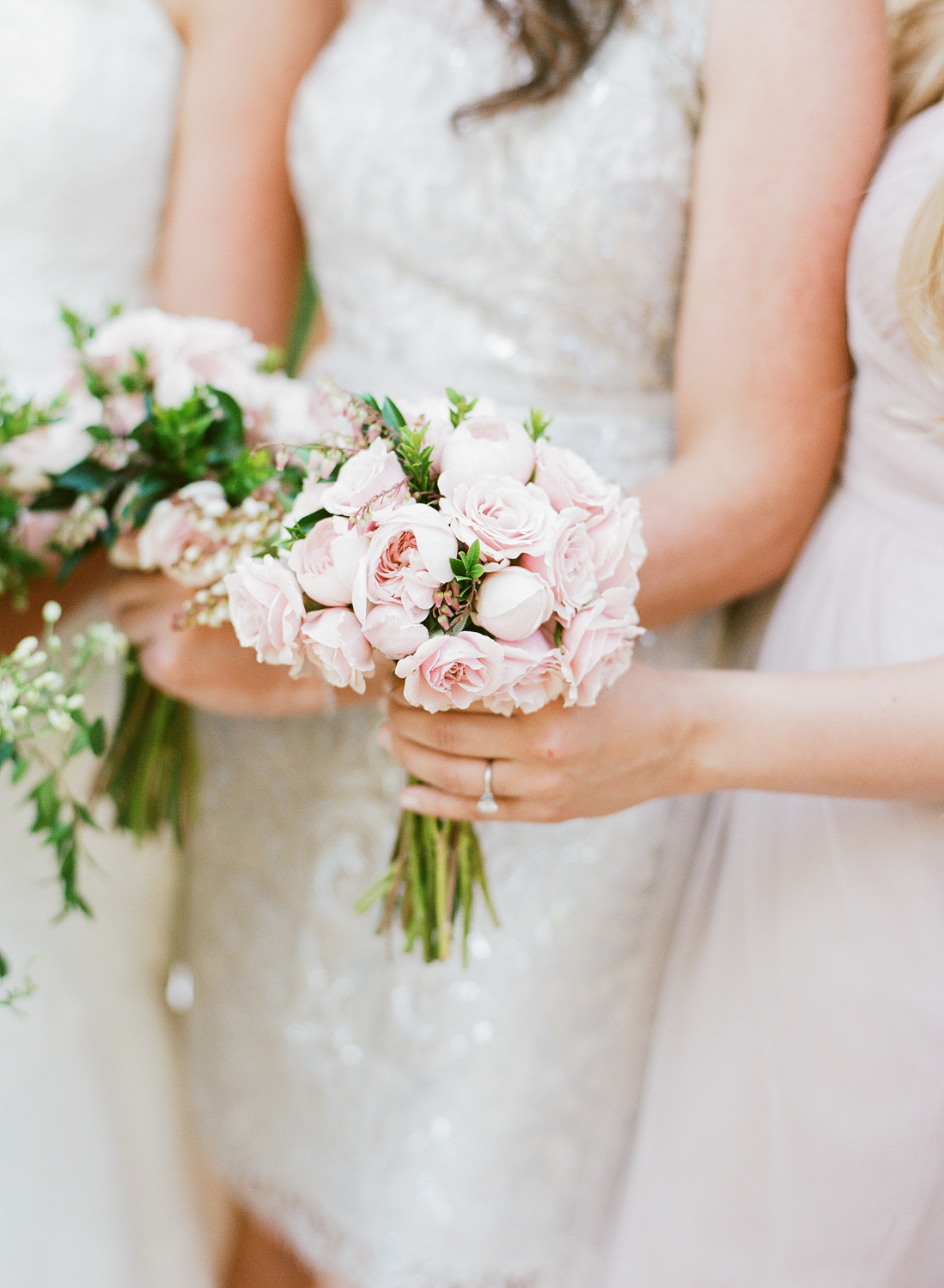 Blush pink roses make up the bridesmaids' bouquets; photo by Sylvie Gil