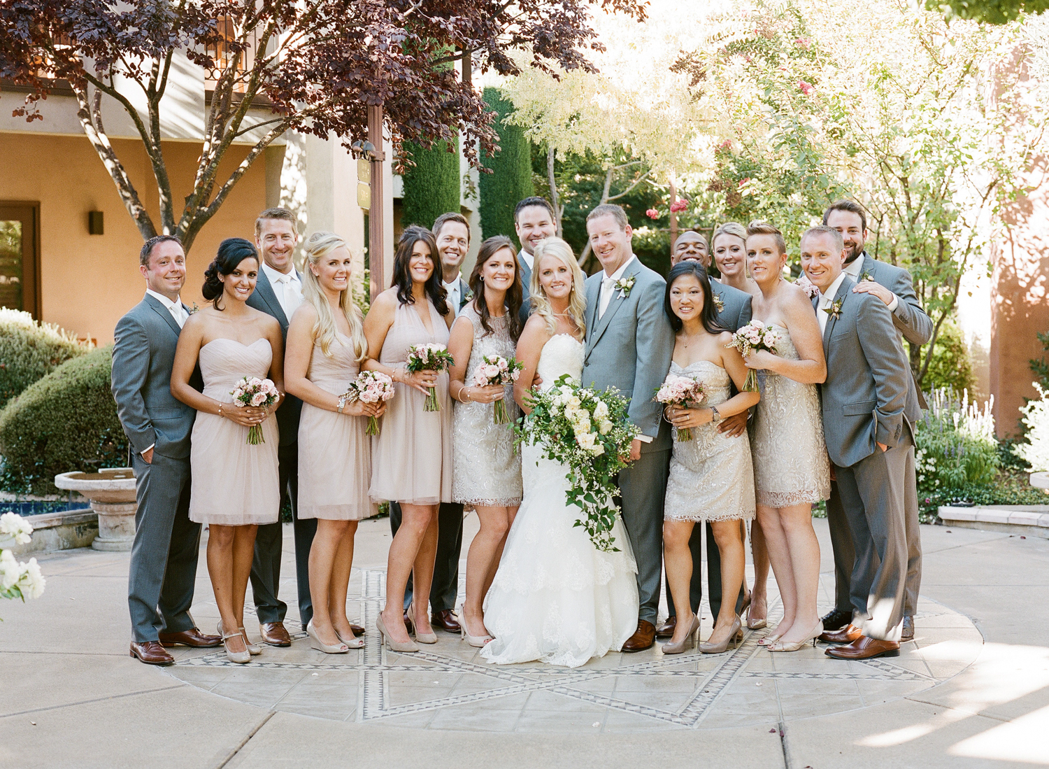 The entire handsome bridal party stands in dappled sunlight, in a gorgeous winery setting; photo by Sylvie Gil