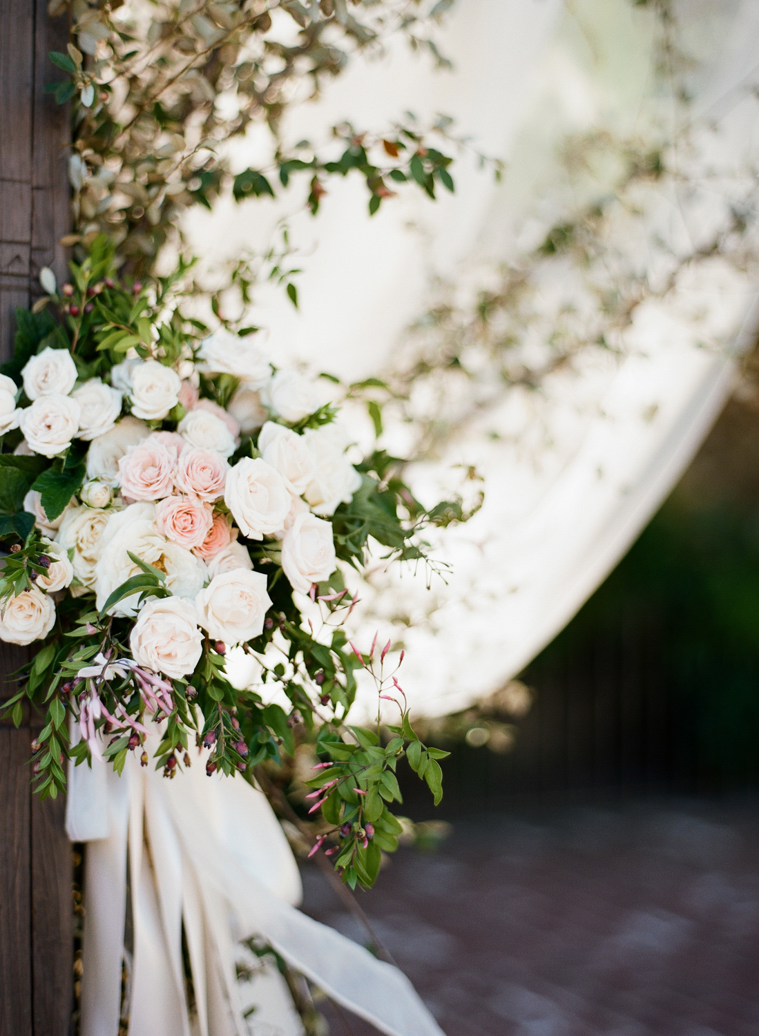 A Max Gill-designed bouquet of blooms and buds decorates a curtain tie at the outdoor reception; photo by Sylvie Gil
