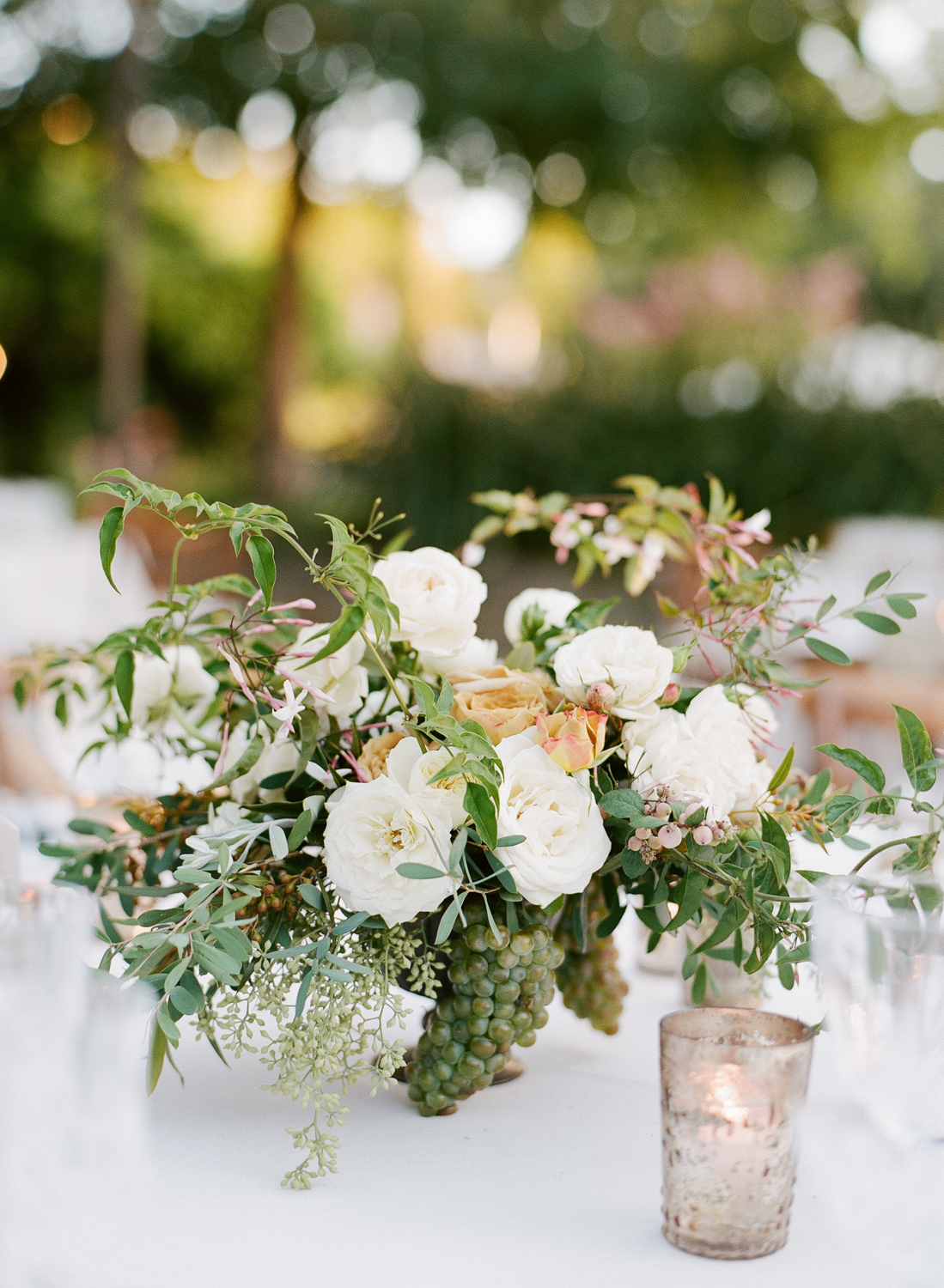 Grapes, among other beautiful accents, make up these Max Gill centerpieces, highlighted by antiqued votive candles; photo by Sylvie Gil