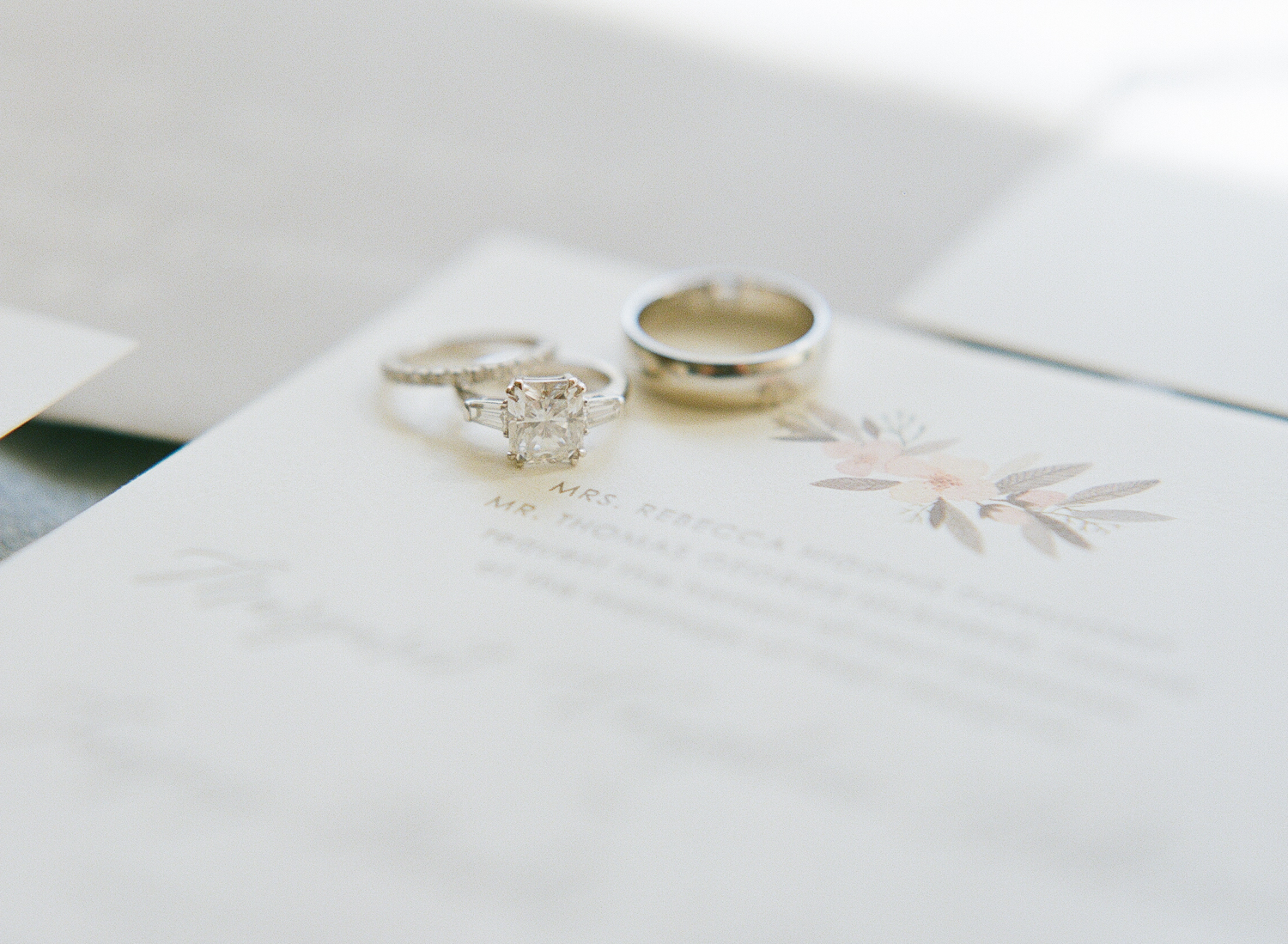 Margo + Tanguy's wedding rings sit atop their darling invitation suite during a pre-wedding shoot by Sylvie Gil