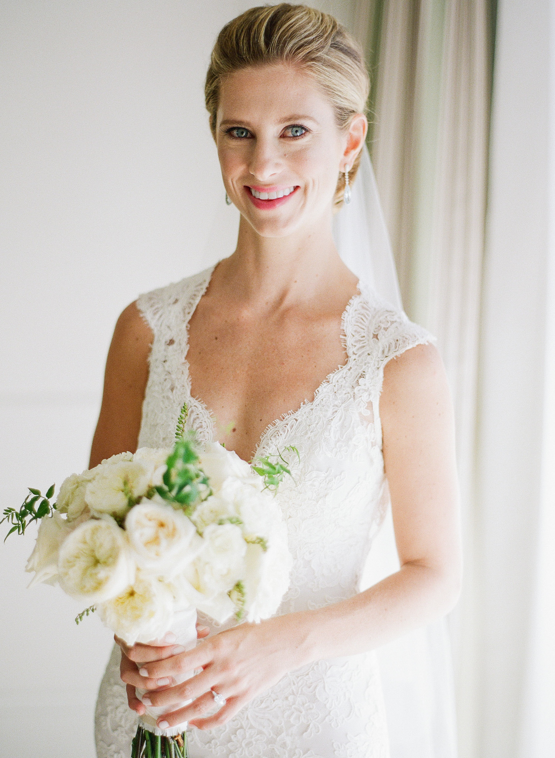 Margo, the beautiful bride, poses in her simple yet elegant lace gown and veil, with a bouquet of cream and olive florals; photo by Sylvie Gil