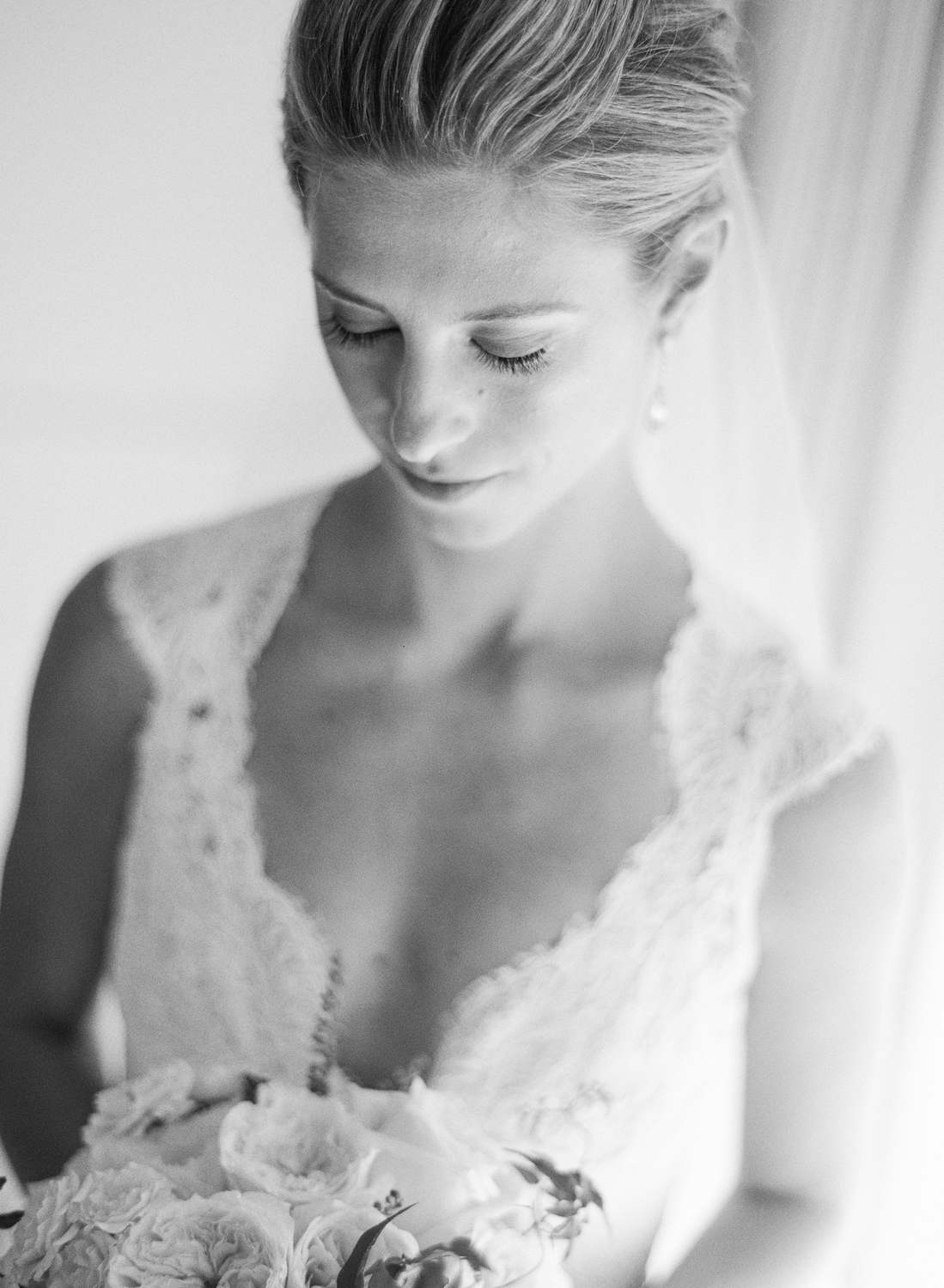 Margo looks down at her gorgeous bouquet before the wedding ceremony; photo by Sylvie Gil