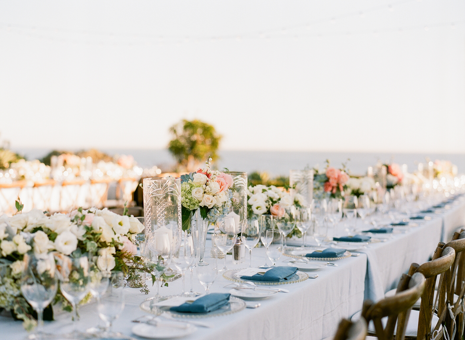 Gorgeous florals and nautical blue linens add to the lovely ocean aesthetic of the Laguna Beach reception; photo by Sylvie Gil