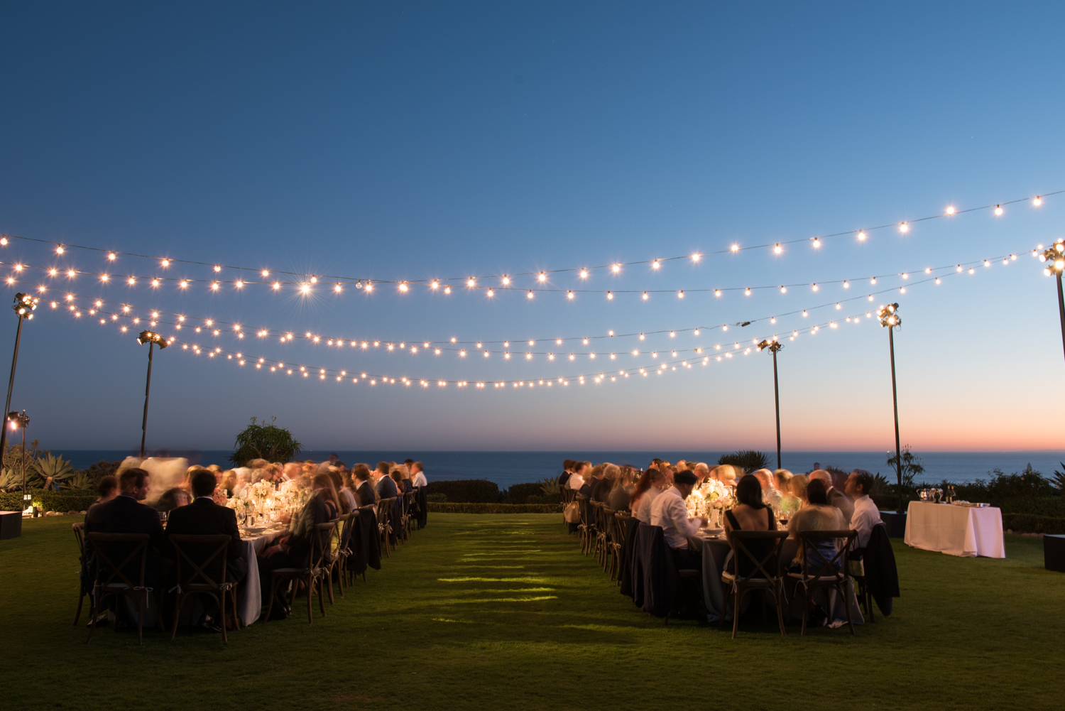 Dusk falls over the outdoor beach reception, guests enjoy dinner lit by romantic string lights; photo by Sylvie Gil