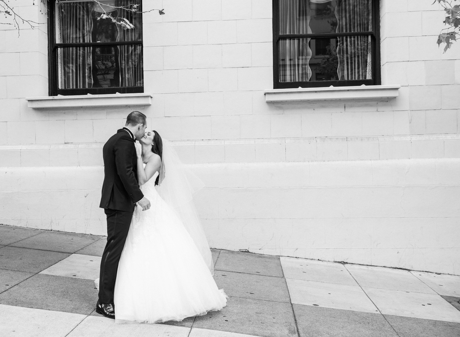 Meg & Ben pause for a kiss on a San Francisco sidewalk during a couple session after their urban wedding; photo by Sylvie Gil