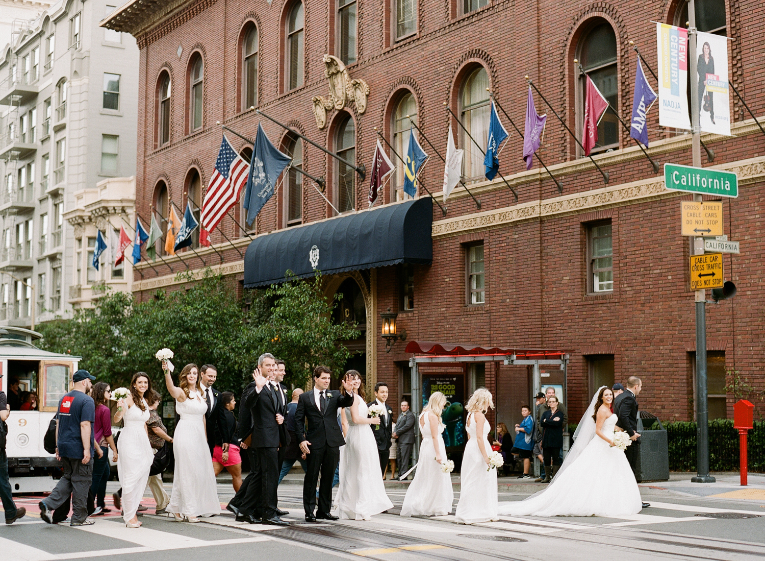 The bridal party waves to the camera as they cross a San Francisco street with passerby; photo by Sylvie Gil