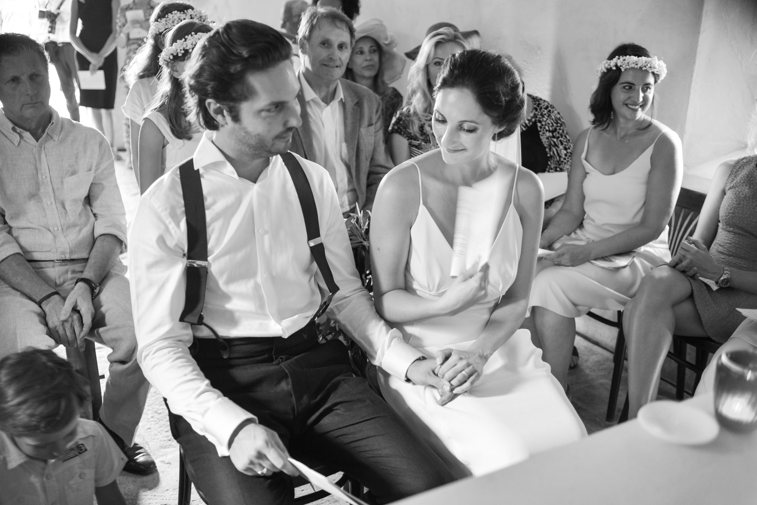 Amelie & Laurent fan themselves sitting hand in hand in a tiny chapel in Provence, France during their wedding ceremony; photo by Sylvie Gil