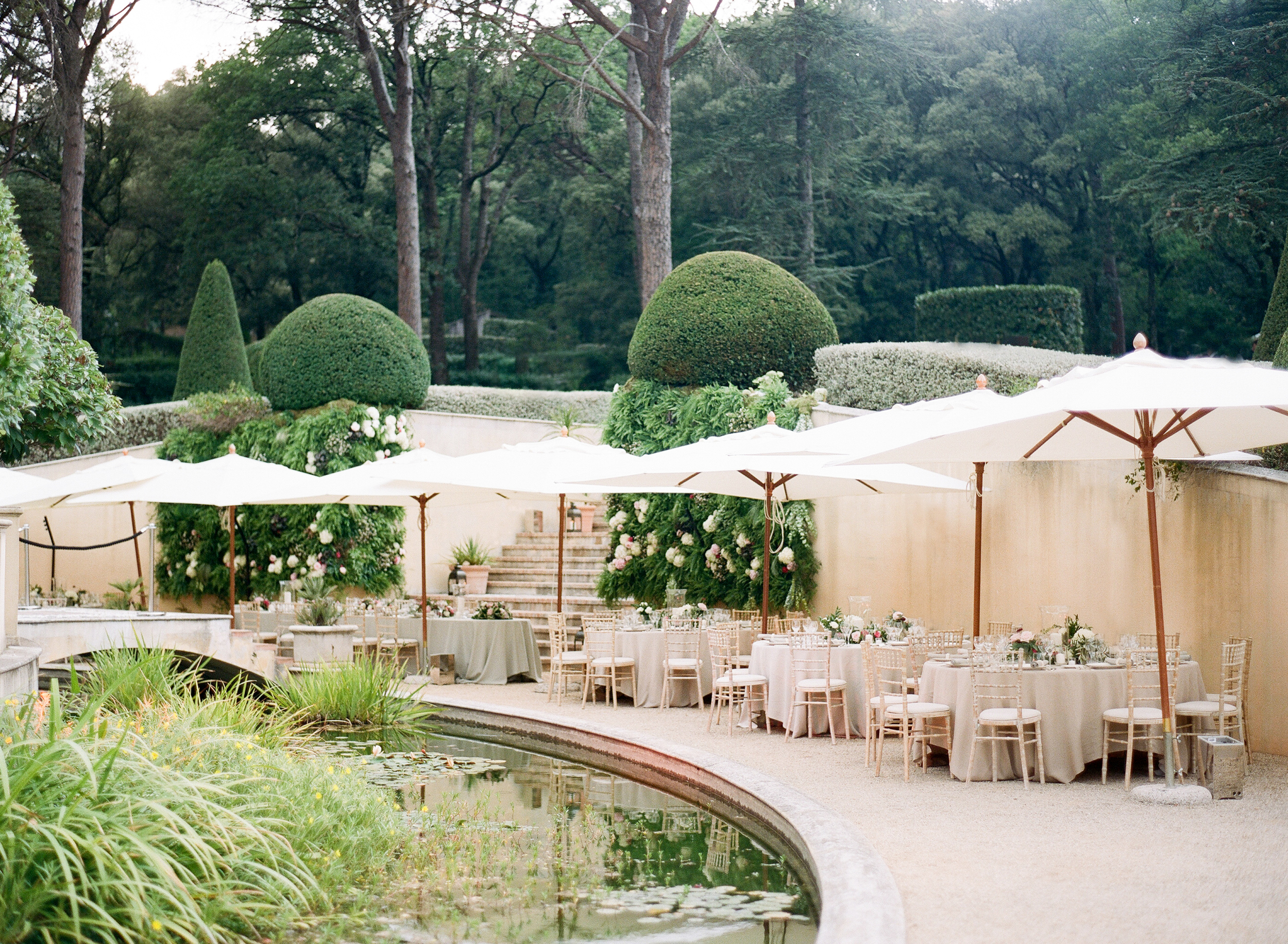 A wide shot of the reception tables by a giant lily pond and next to the dense forest of the estate in Provence, France; photo by Sylvie Gil