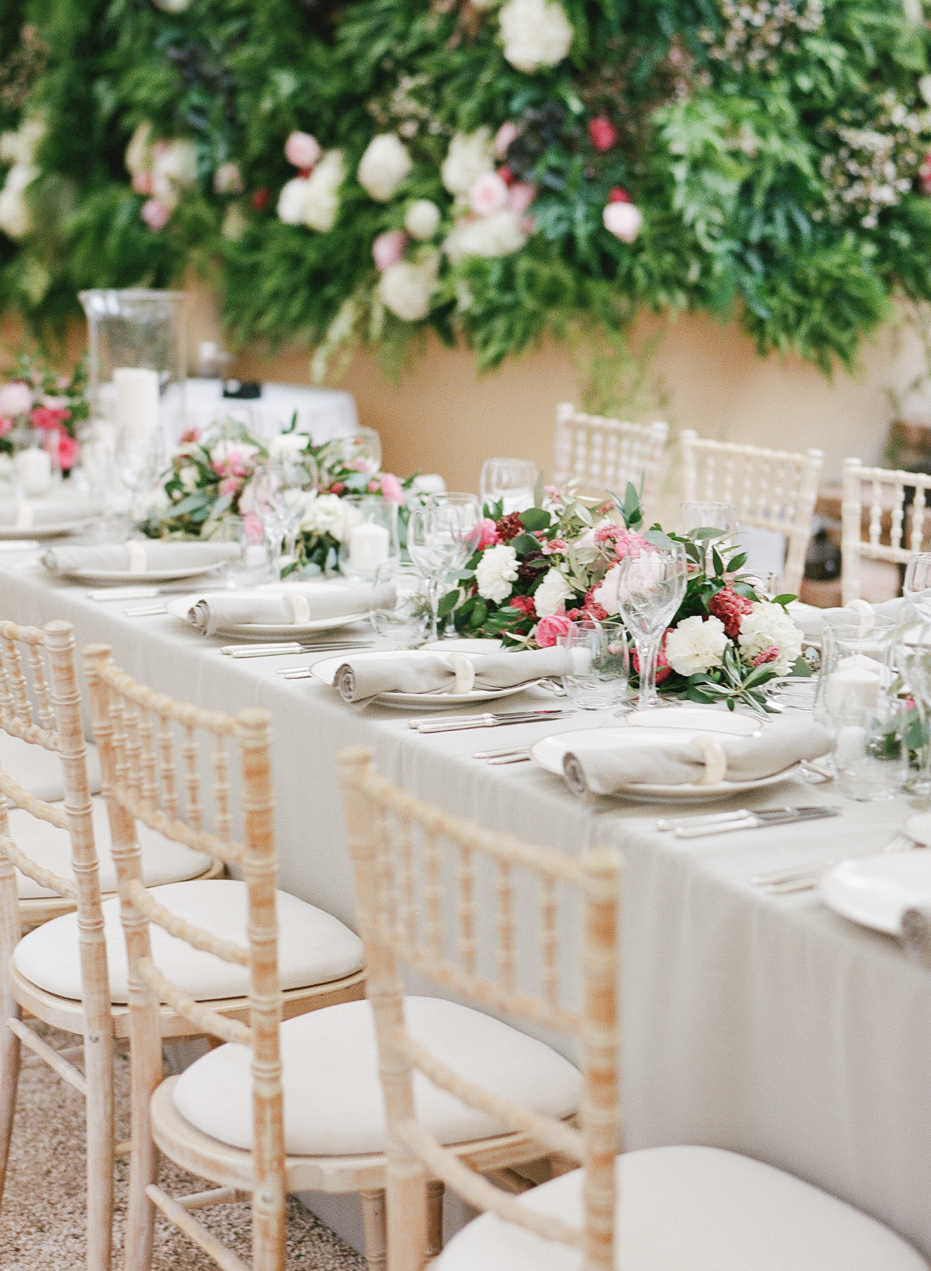 A reception table lined with magenta and cream florals, taupe linens, and gold flatware; photo by Sylvie Gil
