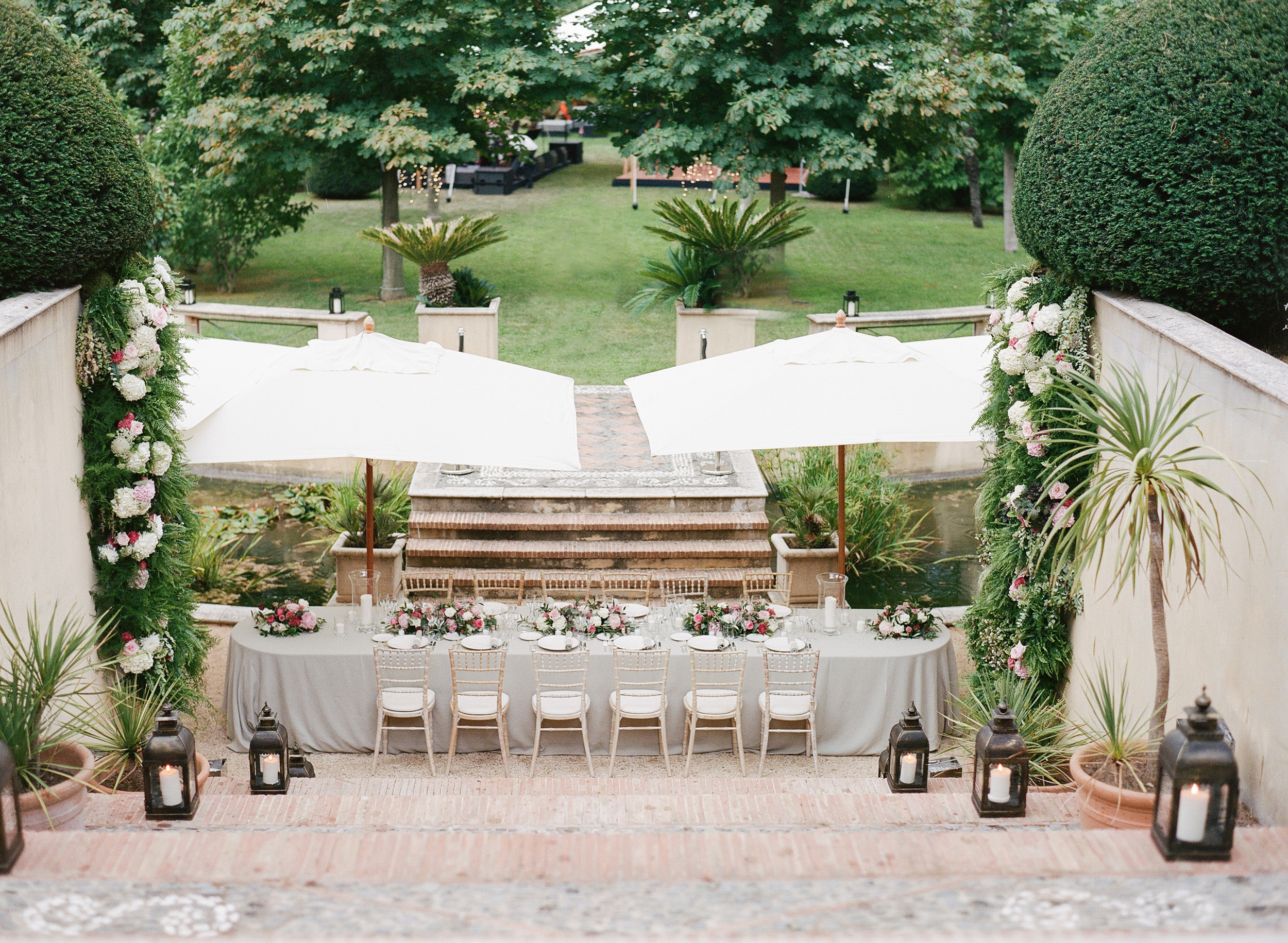 A long reception table lined with floral garlands, lanterns, and shaded by elegant umbrellas; photo by Sylvie Gil