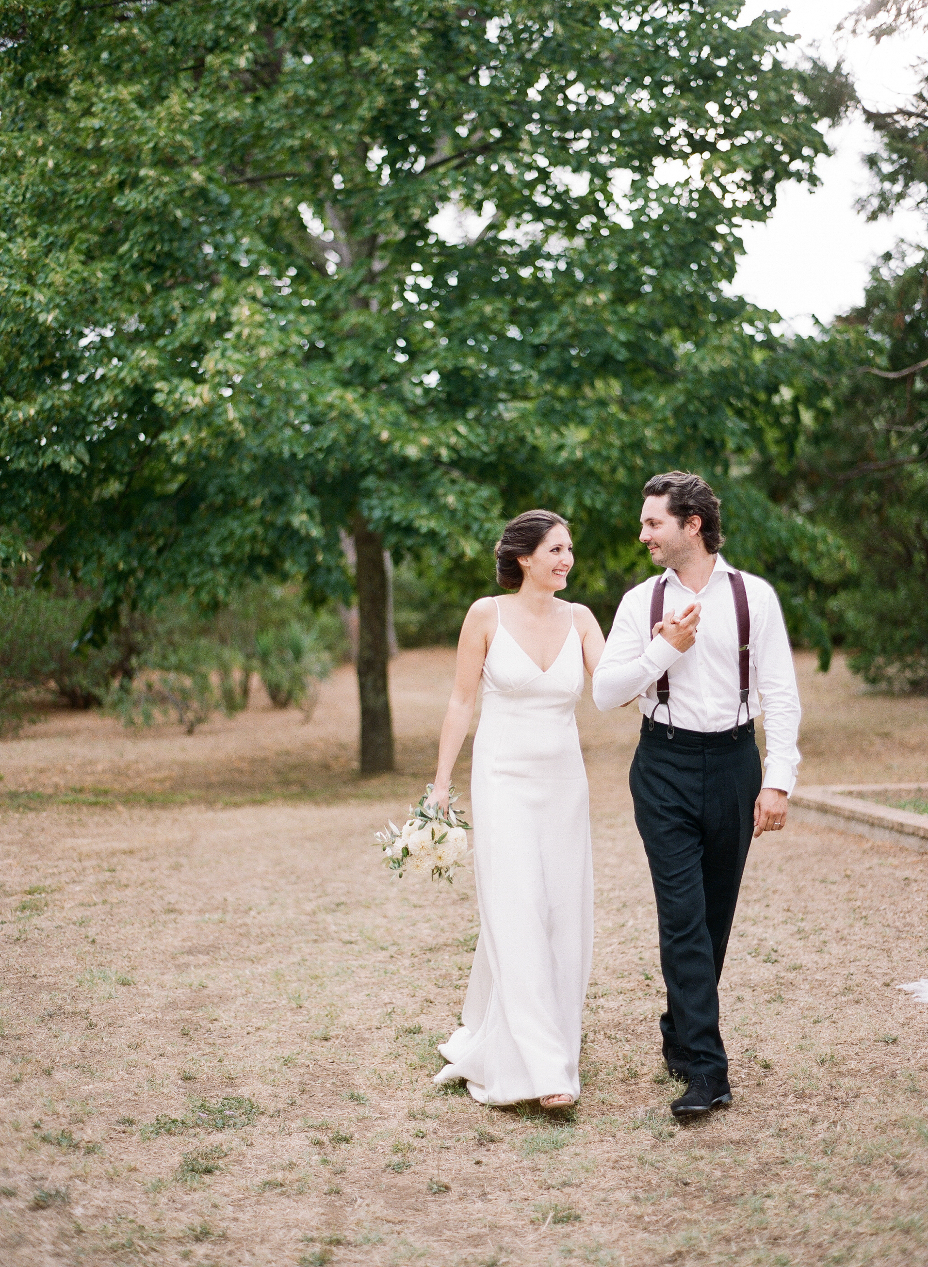 Amelie & Laurent, walk hand in hand as bride and groom, husband and wife, through the beautiful grounds of a private estate in Provence, France, after their wedding ceremony; photo by Sylvie Gil