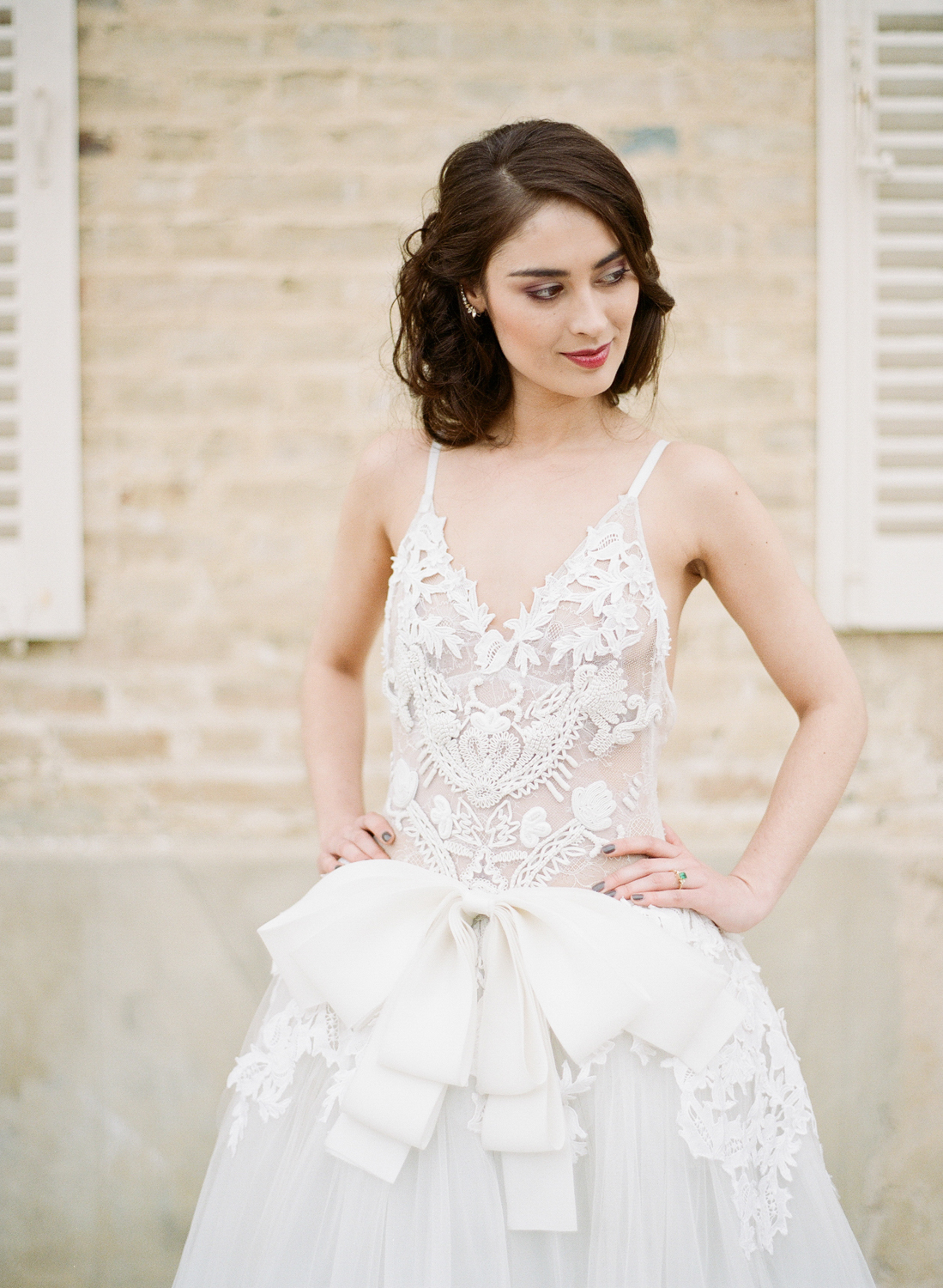 A close up shot of the drop waist, bow-adorned Vera Wang lace gown; photo by Sylvie Gil