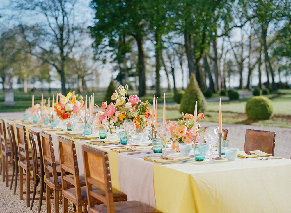 Teal glassware contrasts nicely with pastel florals for a lovely jewel-toned reception table; photo by Sylvie Gil