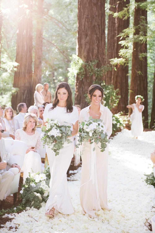 Two bridesmaids walk down the rose-petal-strewn aisle; photo by Sylvie Gil